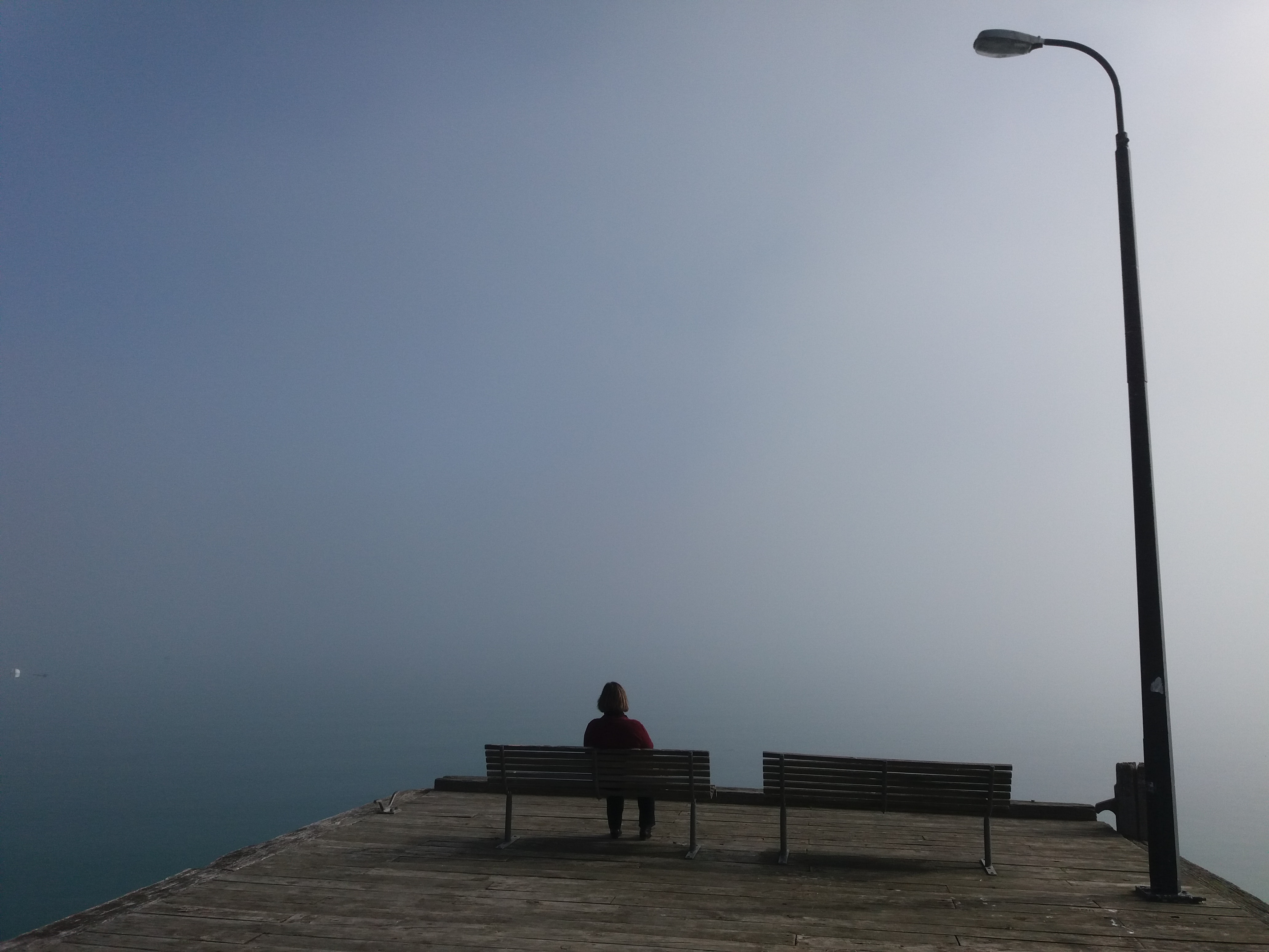 A large street light above a person sitting on one of two park benches.
