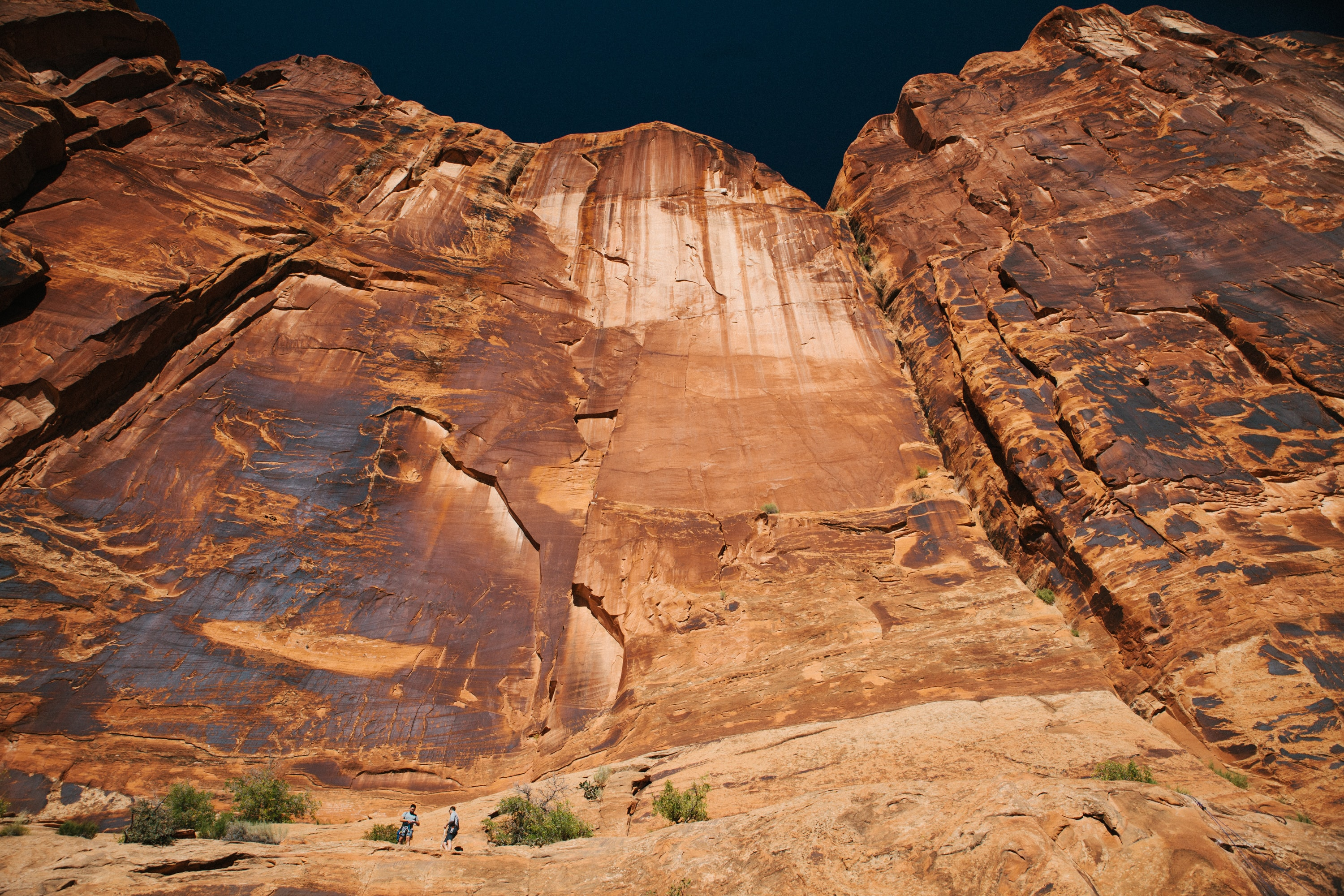 Two people at the foot of a tall vertical face of red rock