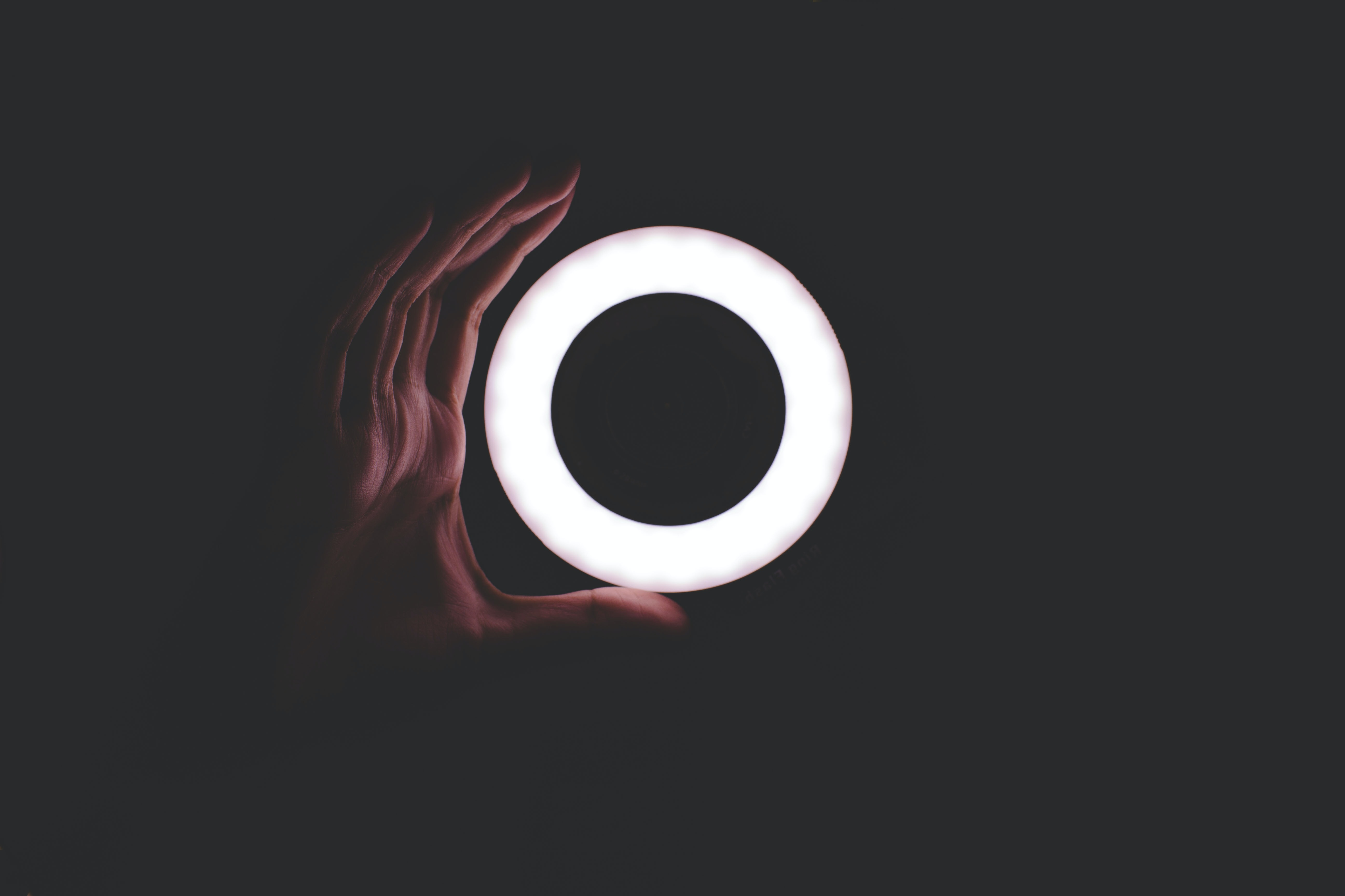A hand taking the shape of a circle light in a black background