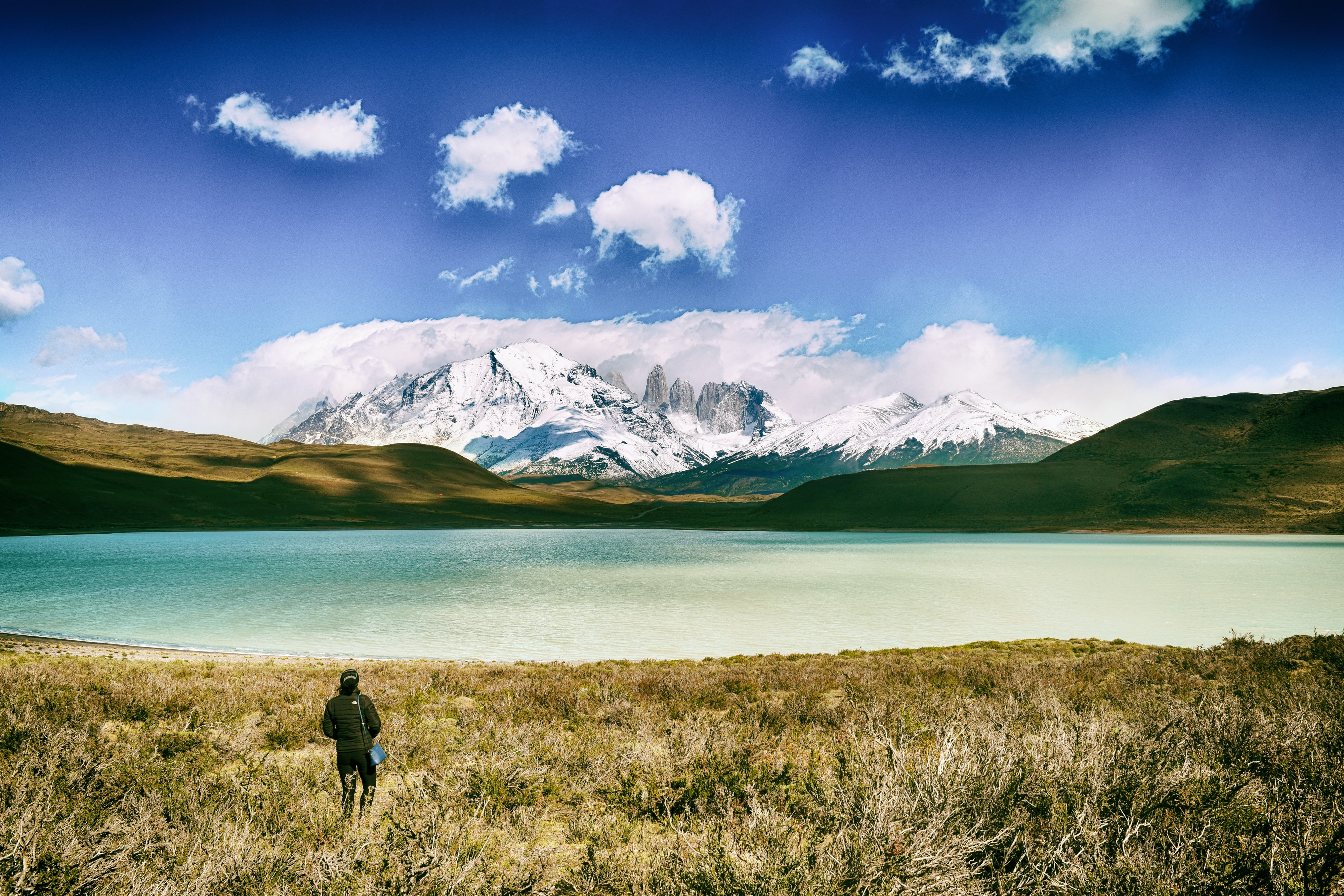 person standing on green grass with green calm body of water near mountains view at daytime