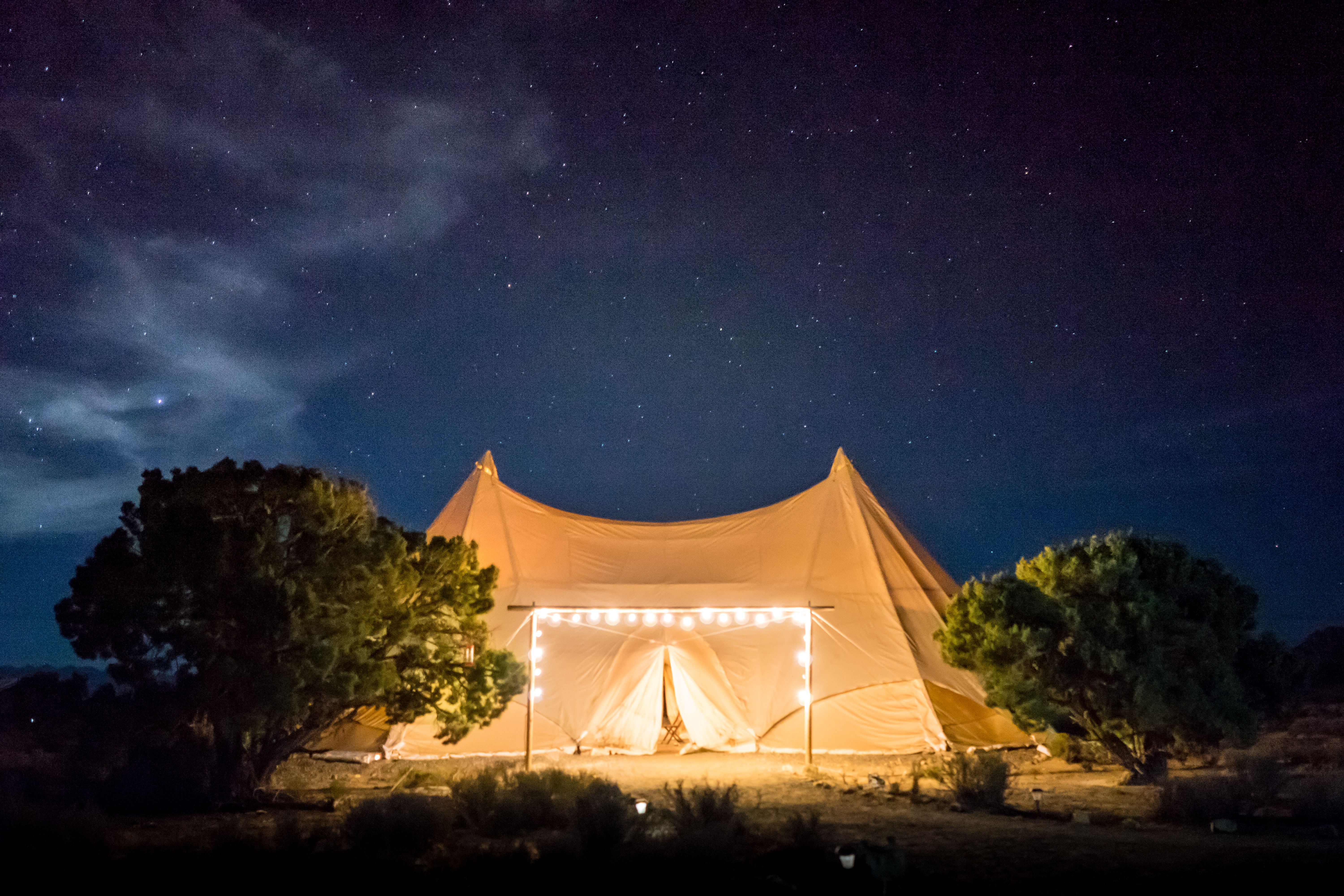 A glamping site surrounded by twinkly lights and trees in the desert under a starry night sky