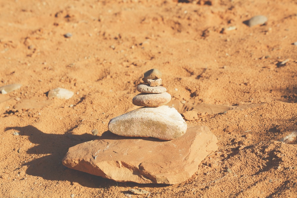 closeup photography of piling stone on sand
