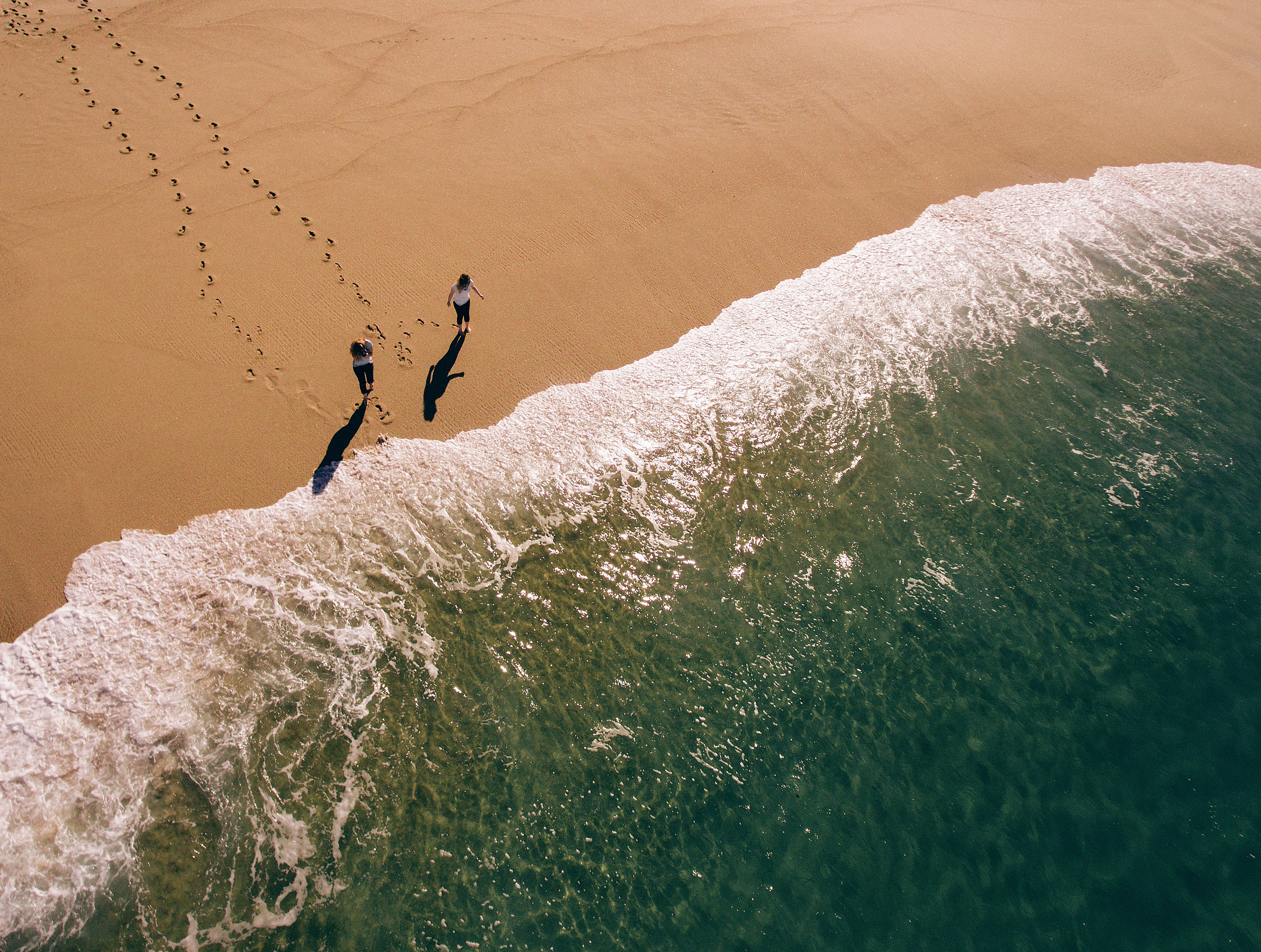 A drone shot of two women walking towards the sea and leaving footprints in the wet sand