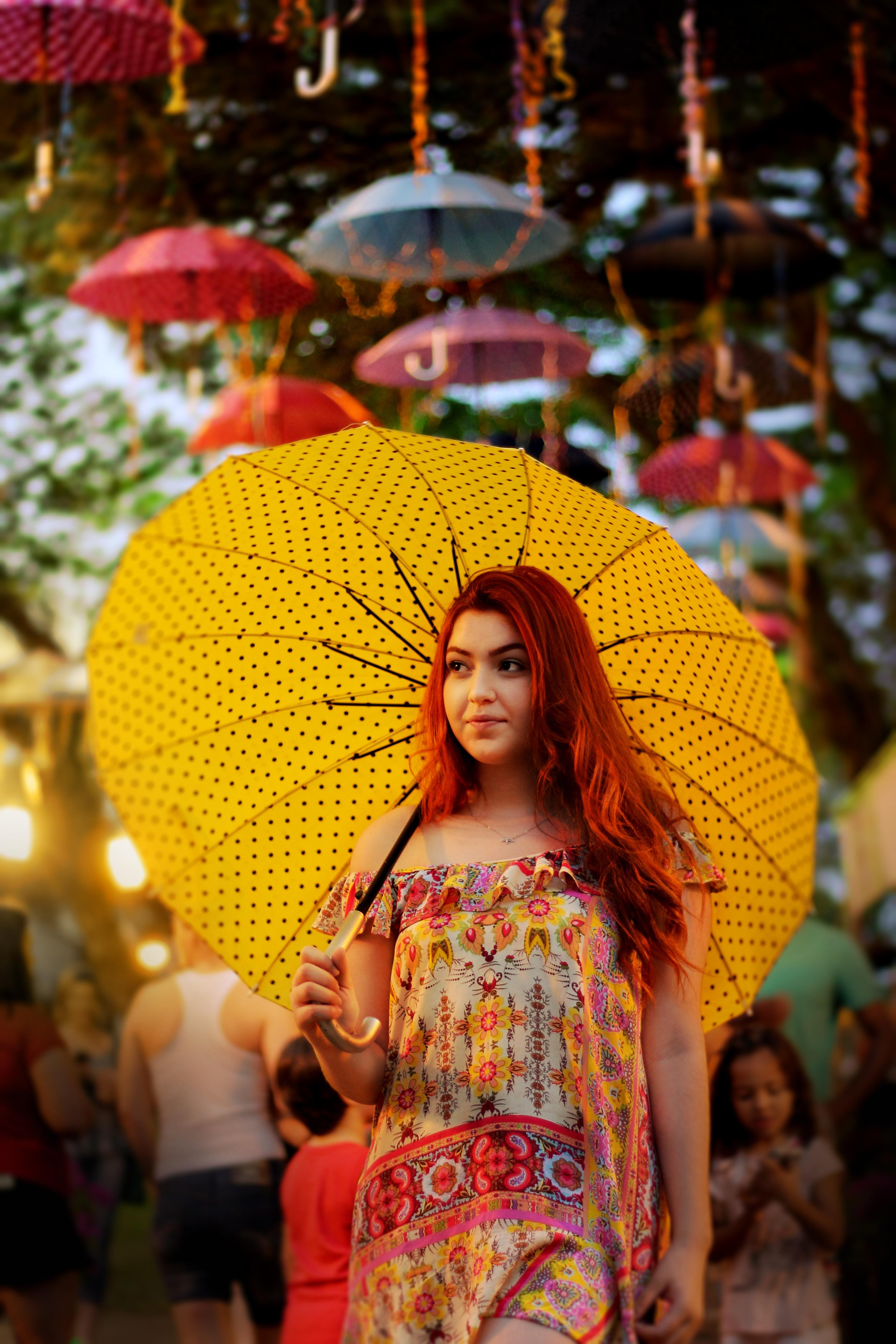 An Asian redhead female holding a yellow umbrella.