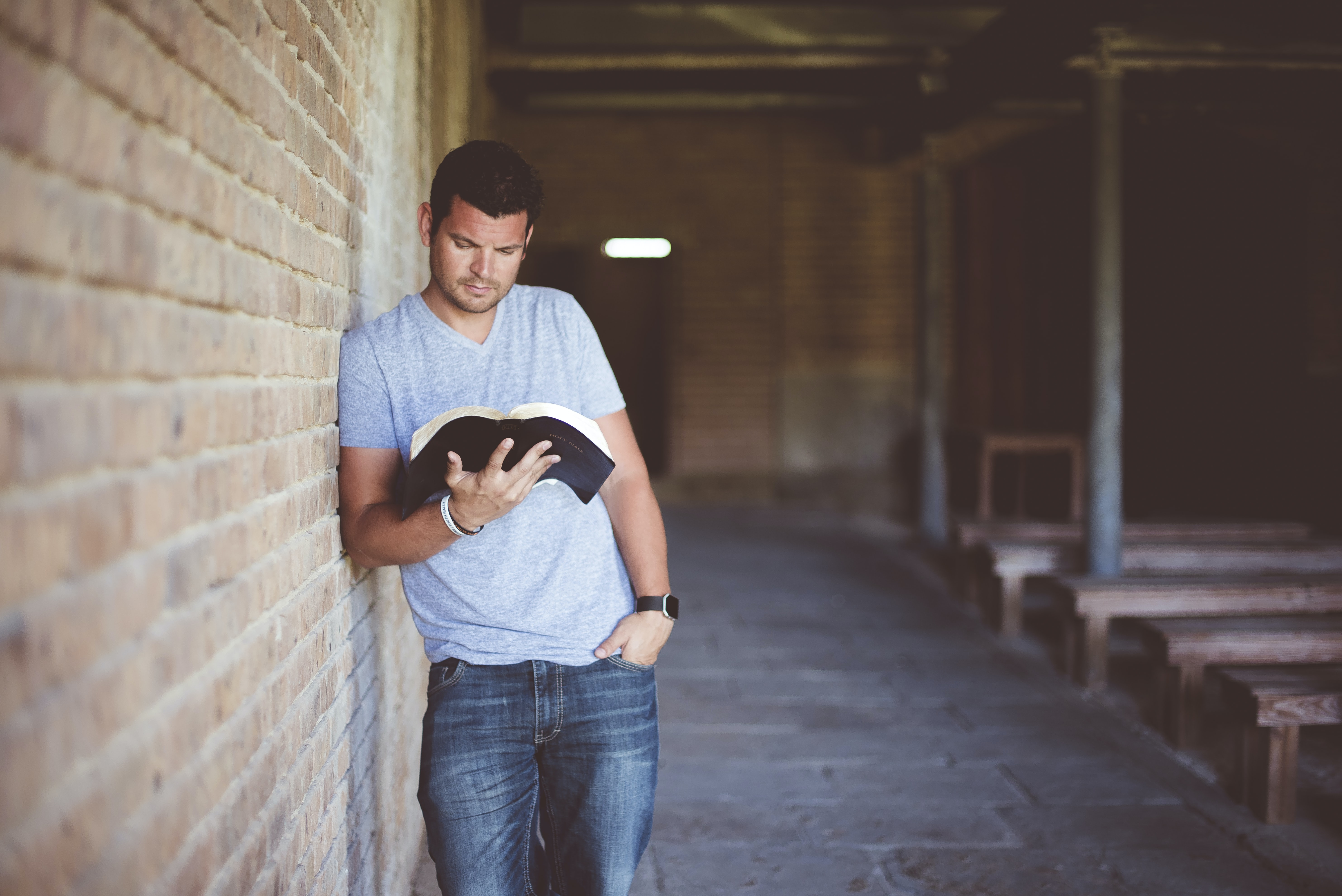 A man leaning against a wall outside while reading a book.