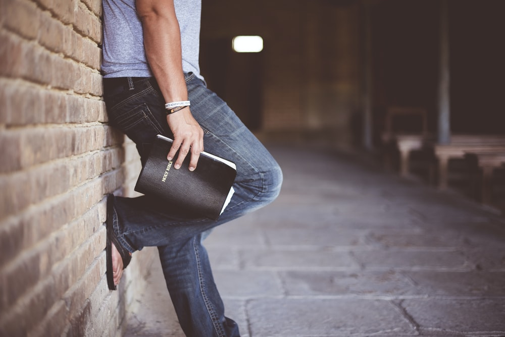man holding Holy Bible leaning on bricked wall