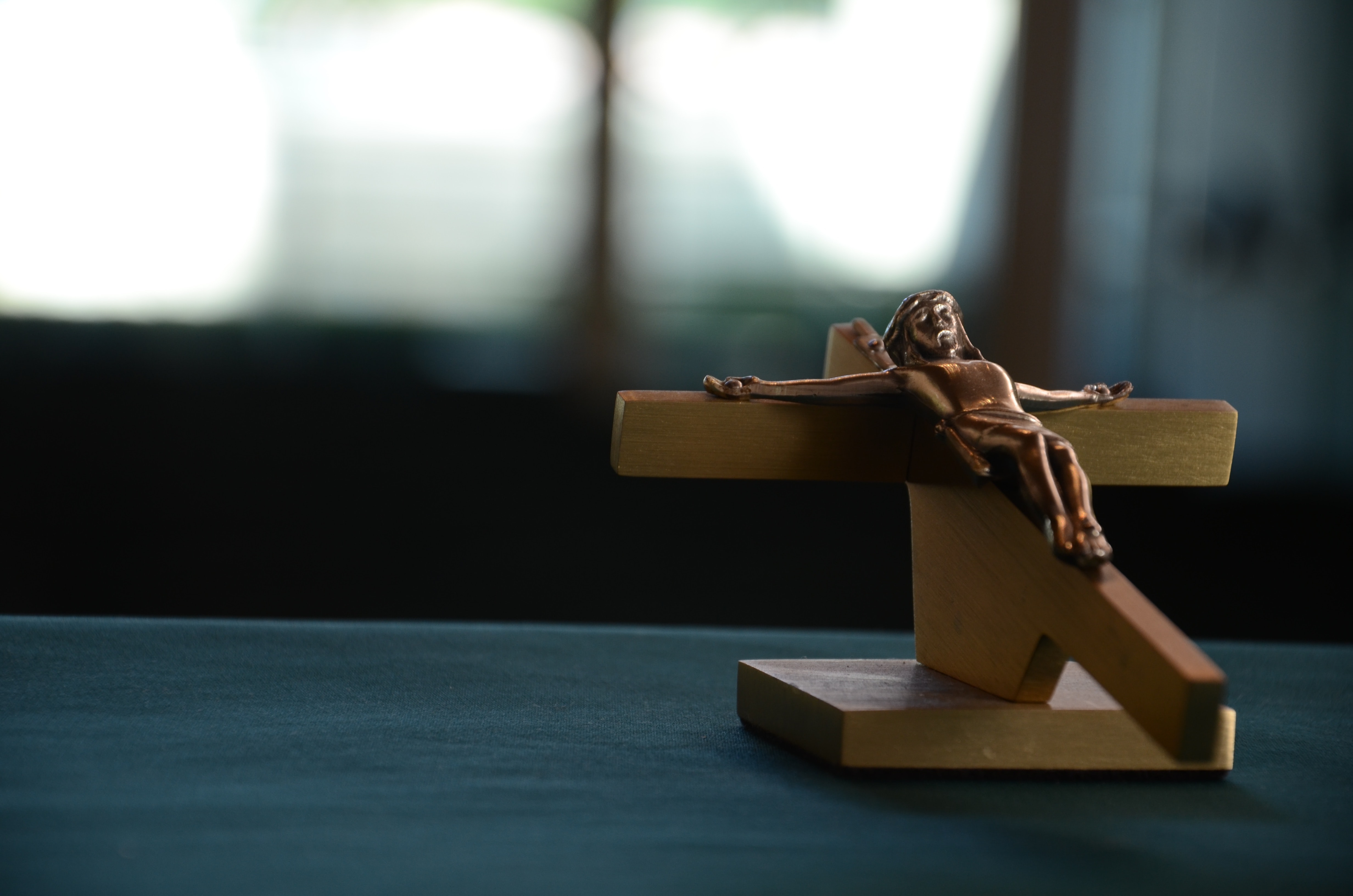 Wooden crucifix with figure of Jesus laying on a dark table