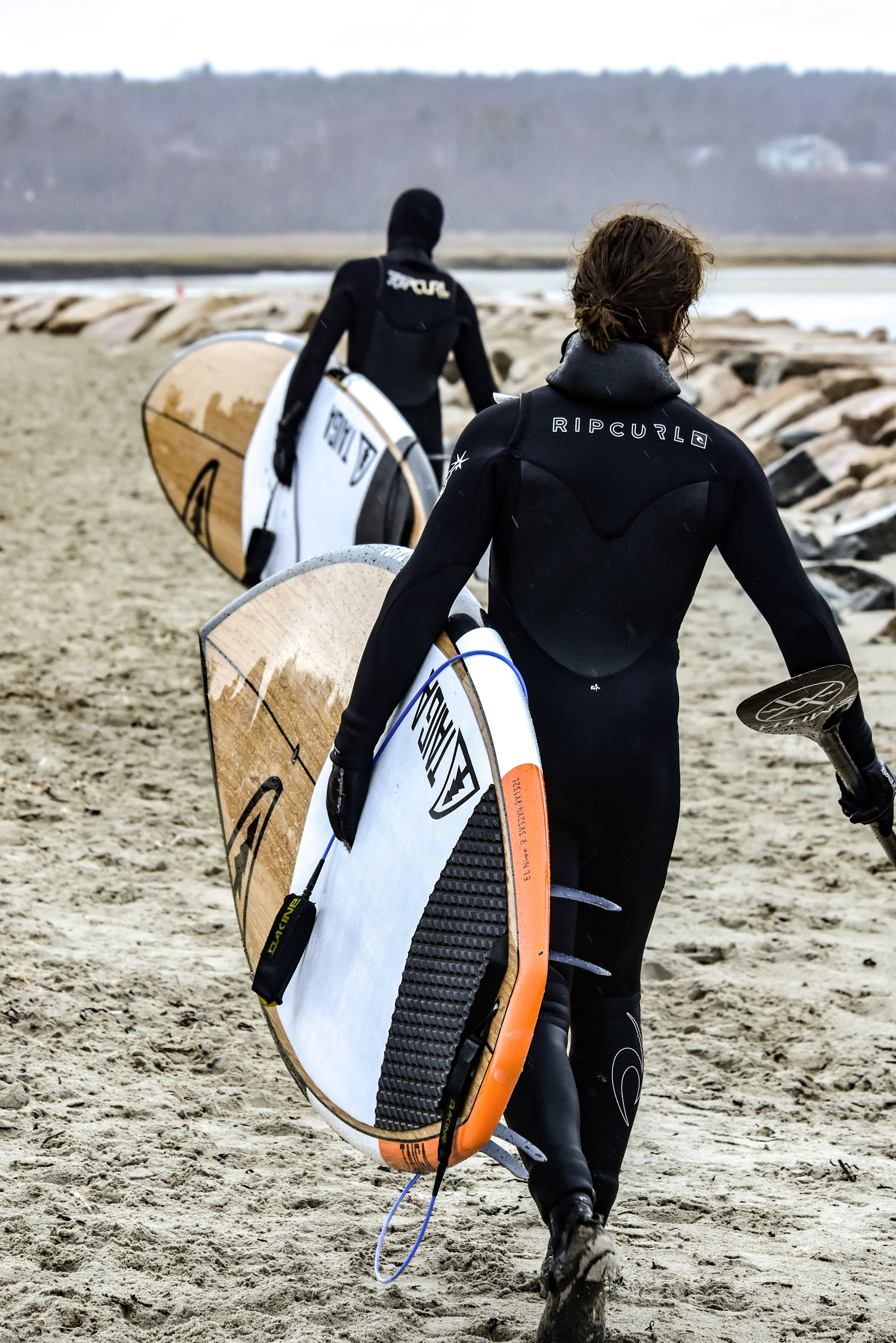 Two male paddleboarders wearing wetsuits walking along the beach at Wells, carrying their boards under their arms