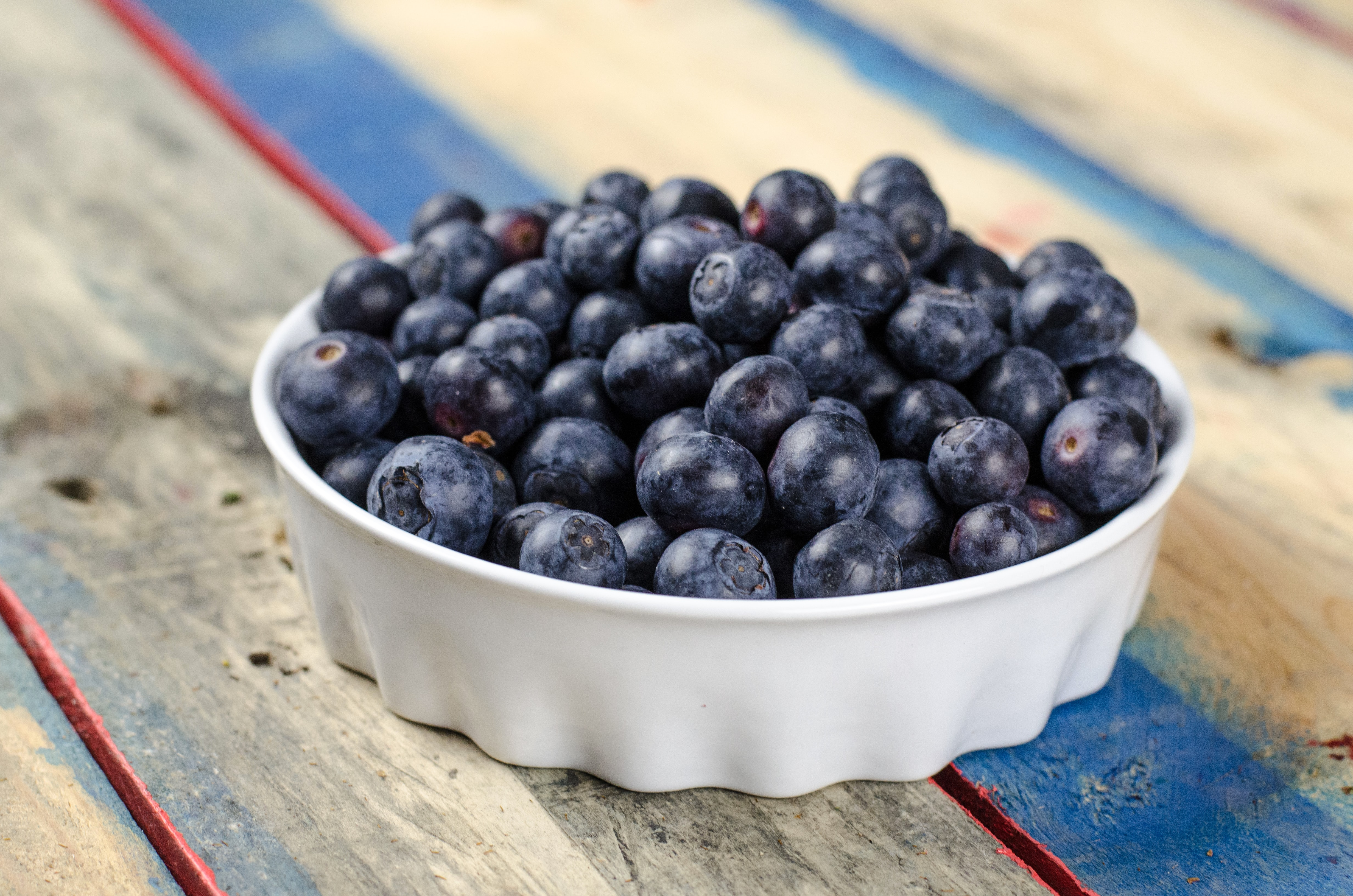 A simple white bowl filled with blueberries on a wooden picnic table in Versailles