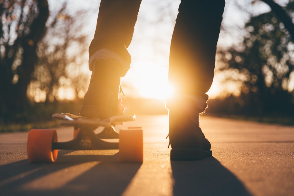 man putting left foot on longboard against sunglight