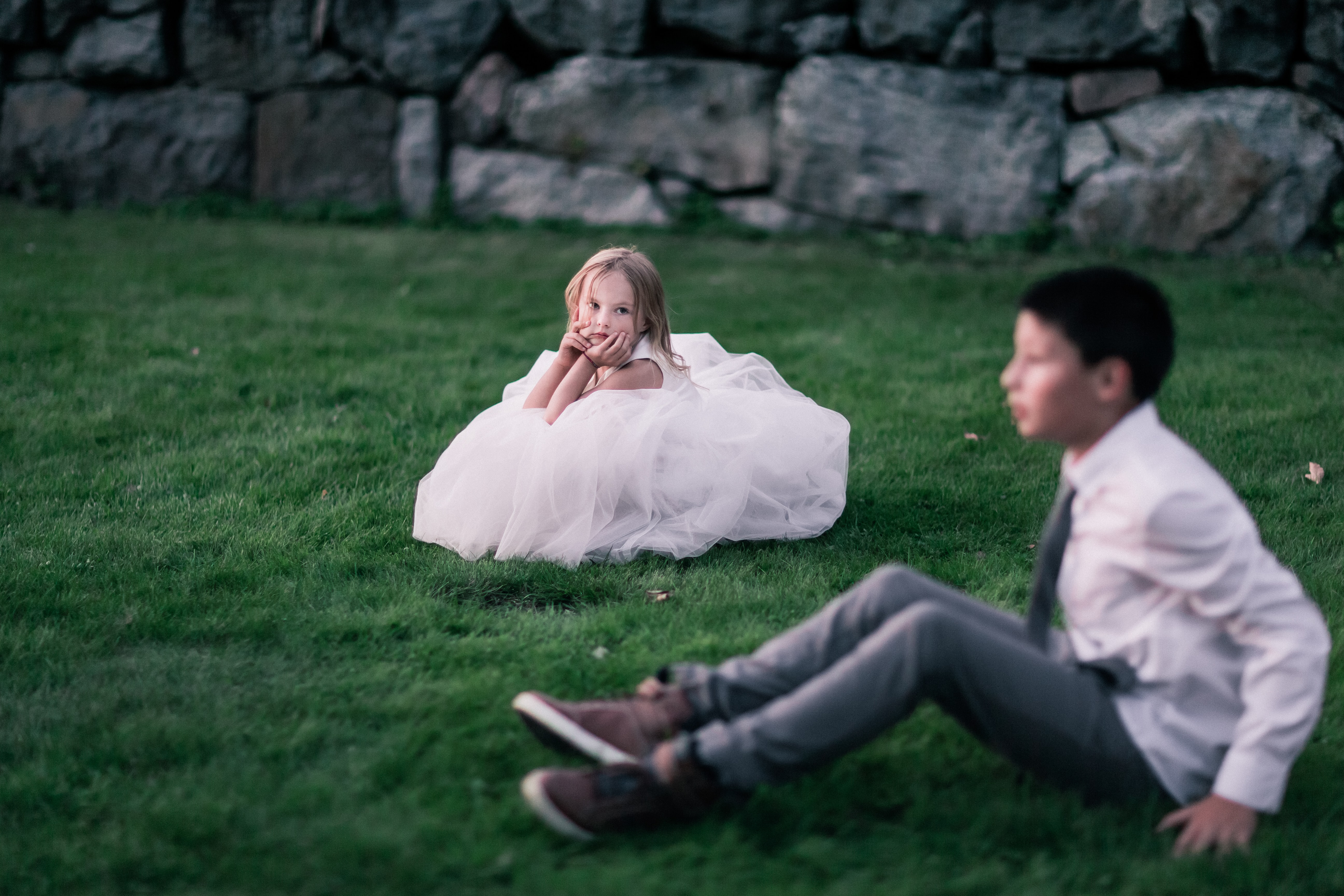 Young girl and boy dressed up in wedding clothes sitting in a field