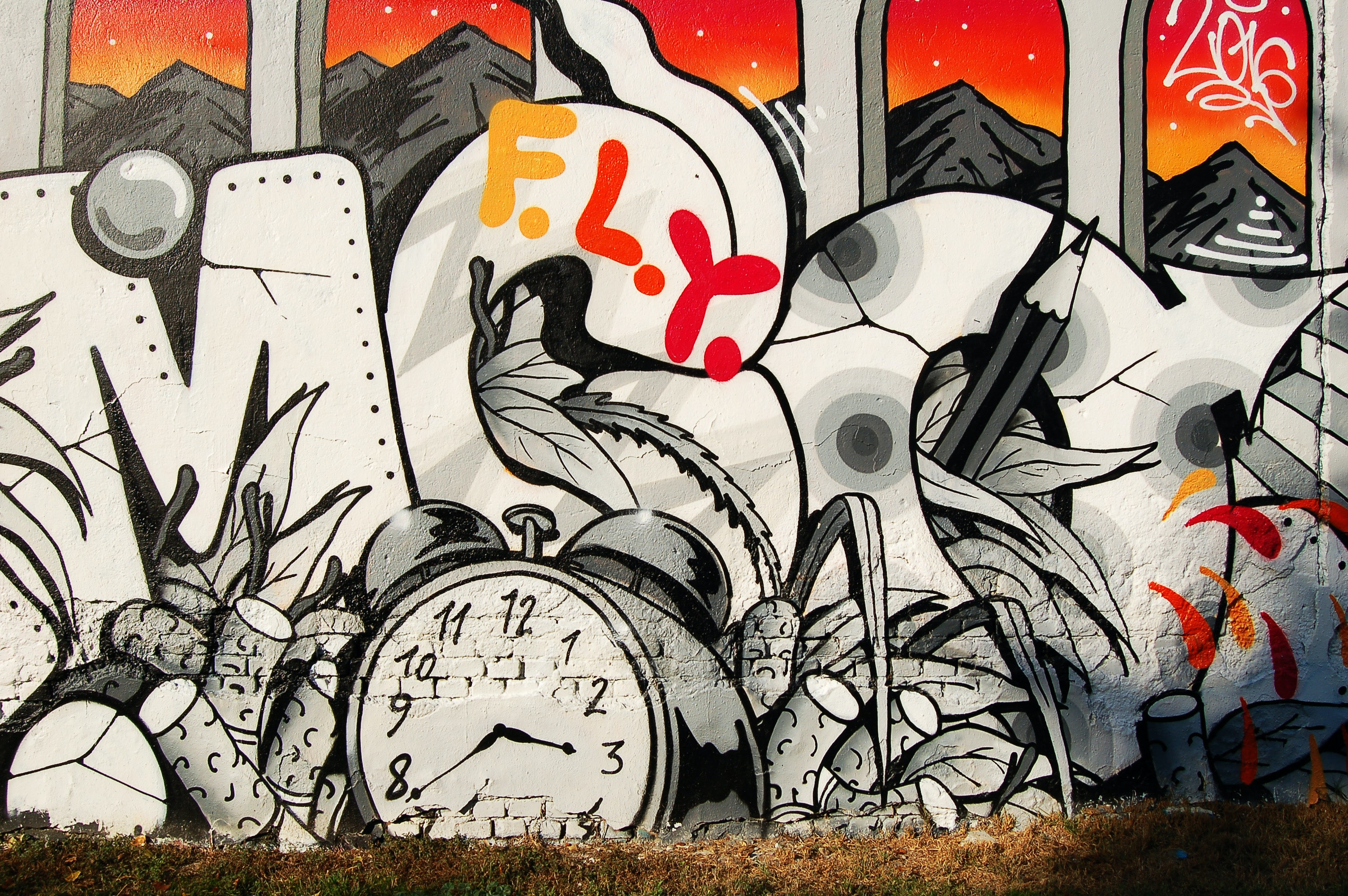 Graffiti writing on a wall with a clock and dynamite.