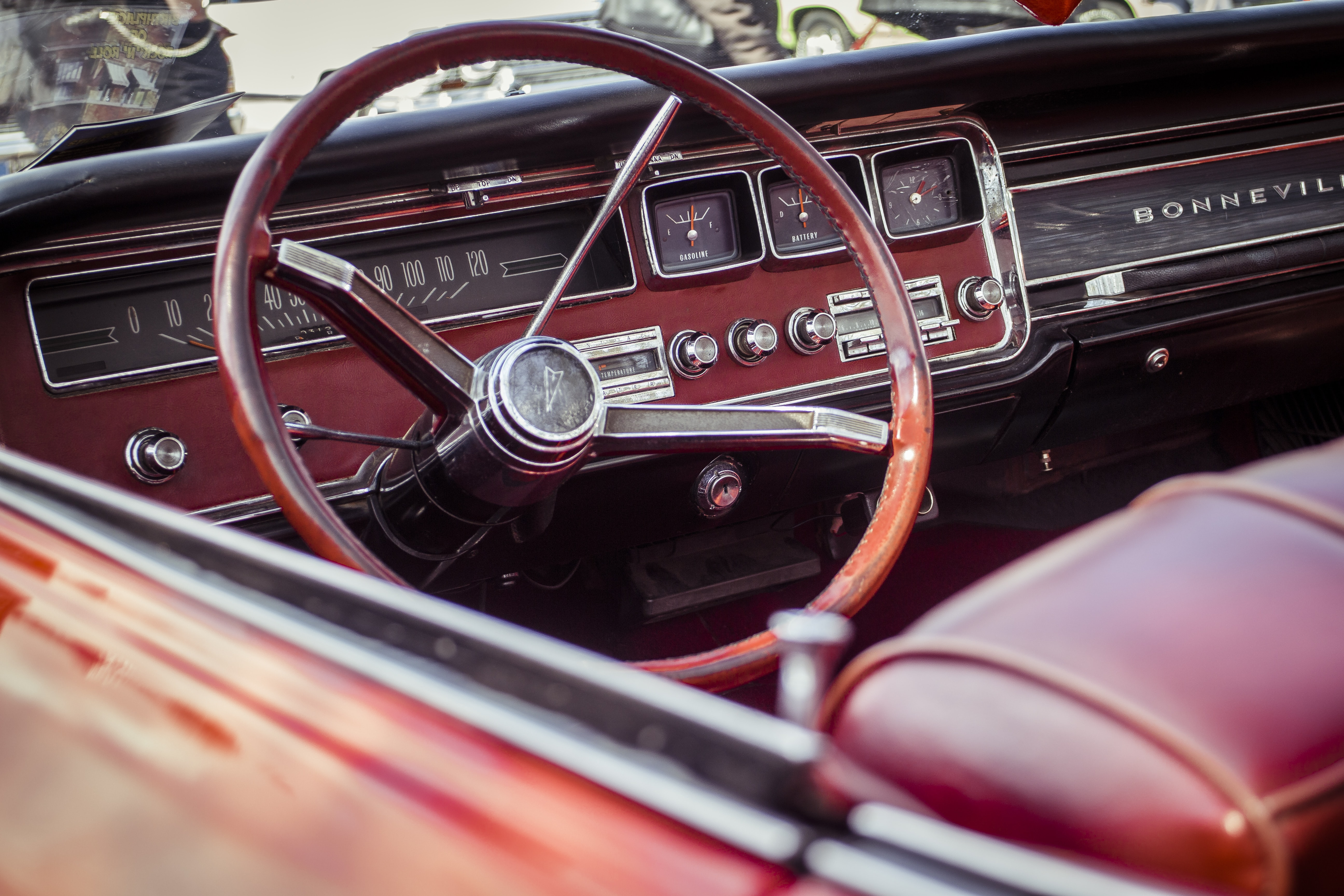 Steering wheel of a red vintage car with red interior.