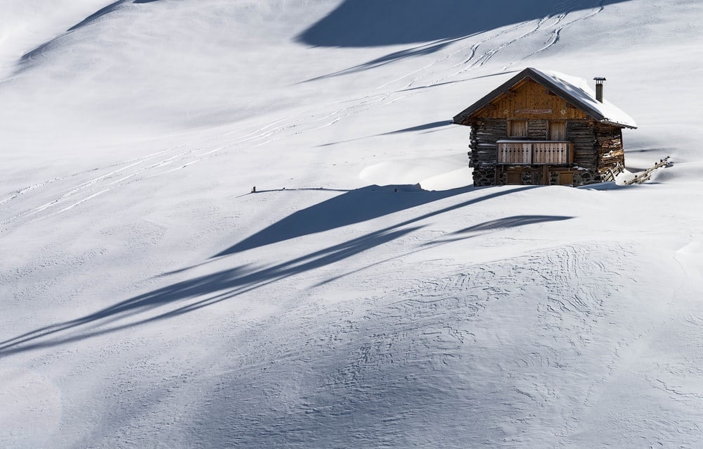 brown wooden house covered of snow