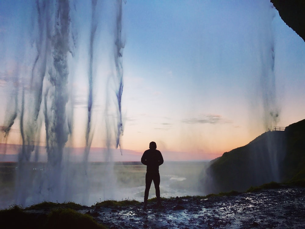 silhouette on man standing near body of water