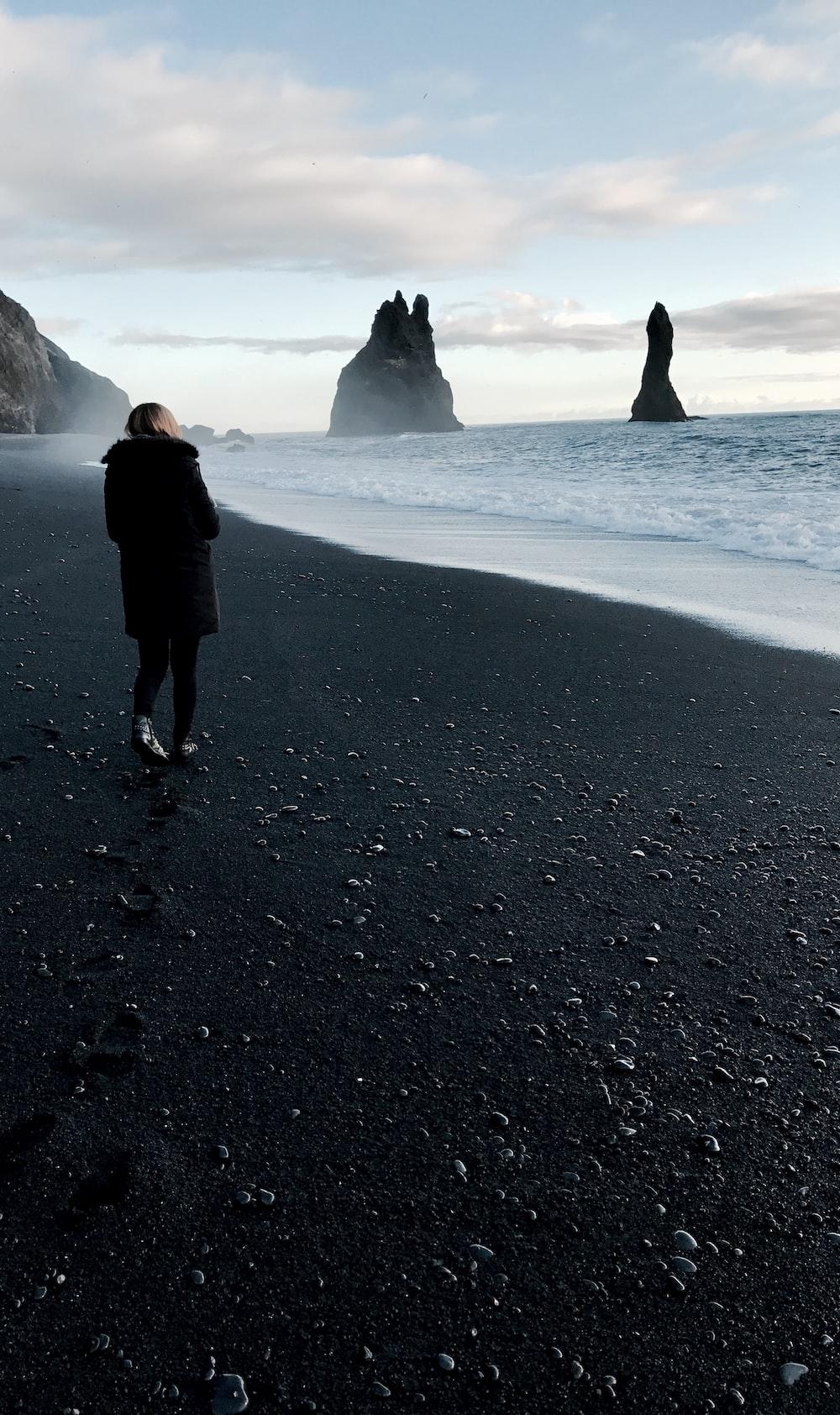 person walking near body of water