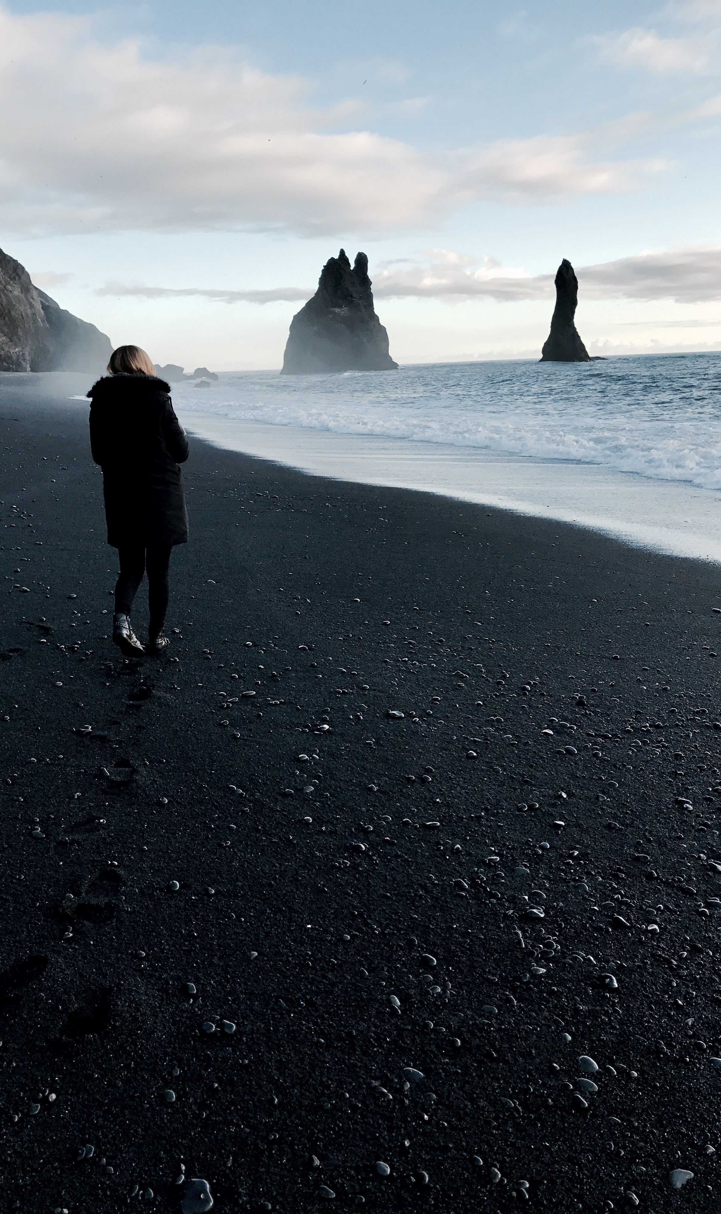 Woman in black coat standing on a black sand beach looking at the ocean in Iceland