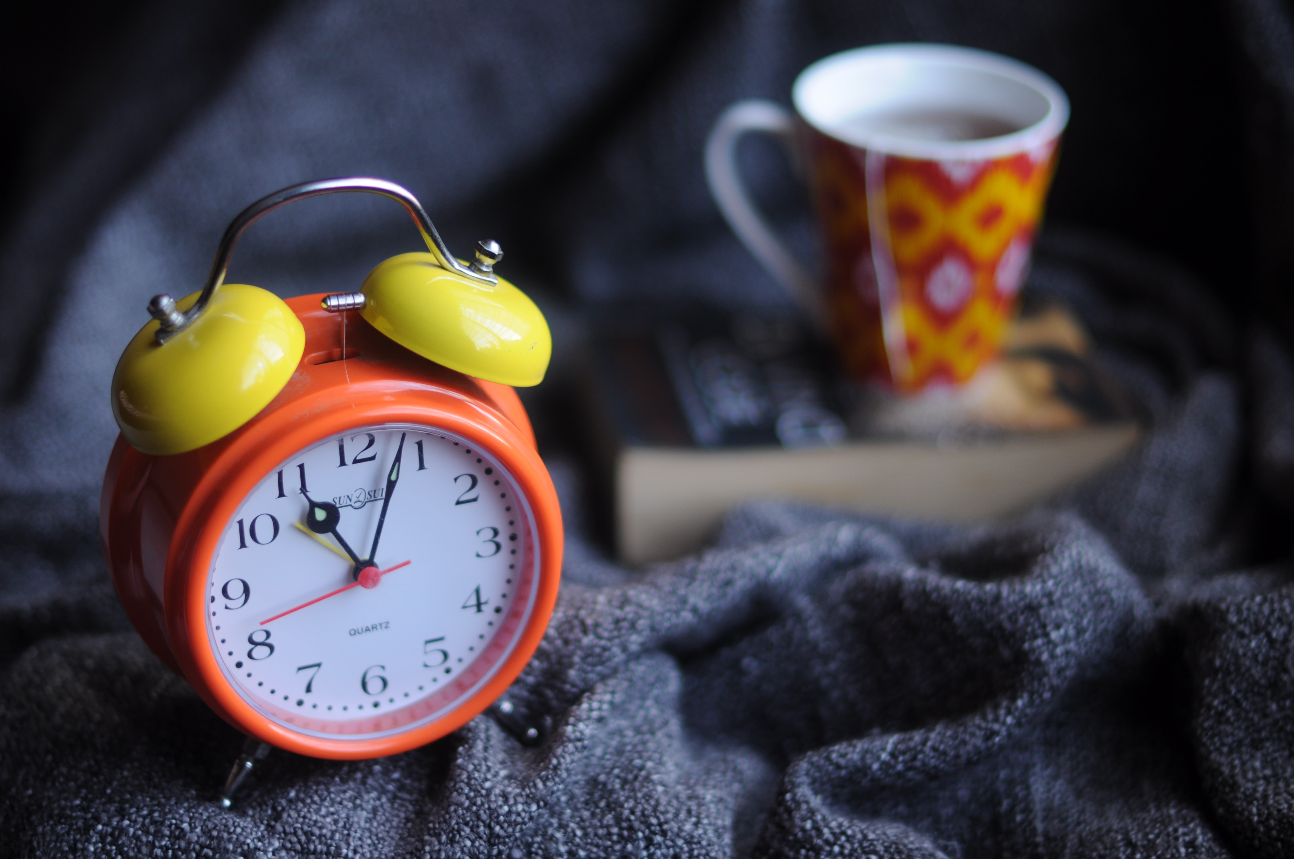 A macro shot of a standard alarm clock, cup of coffee and a large book