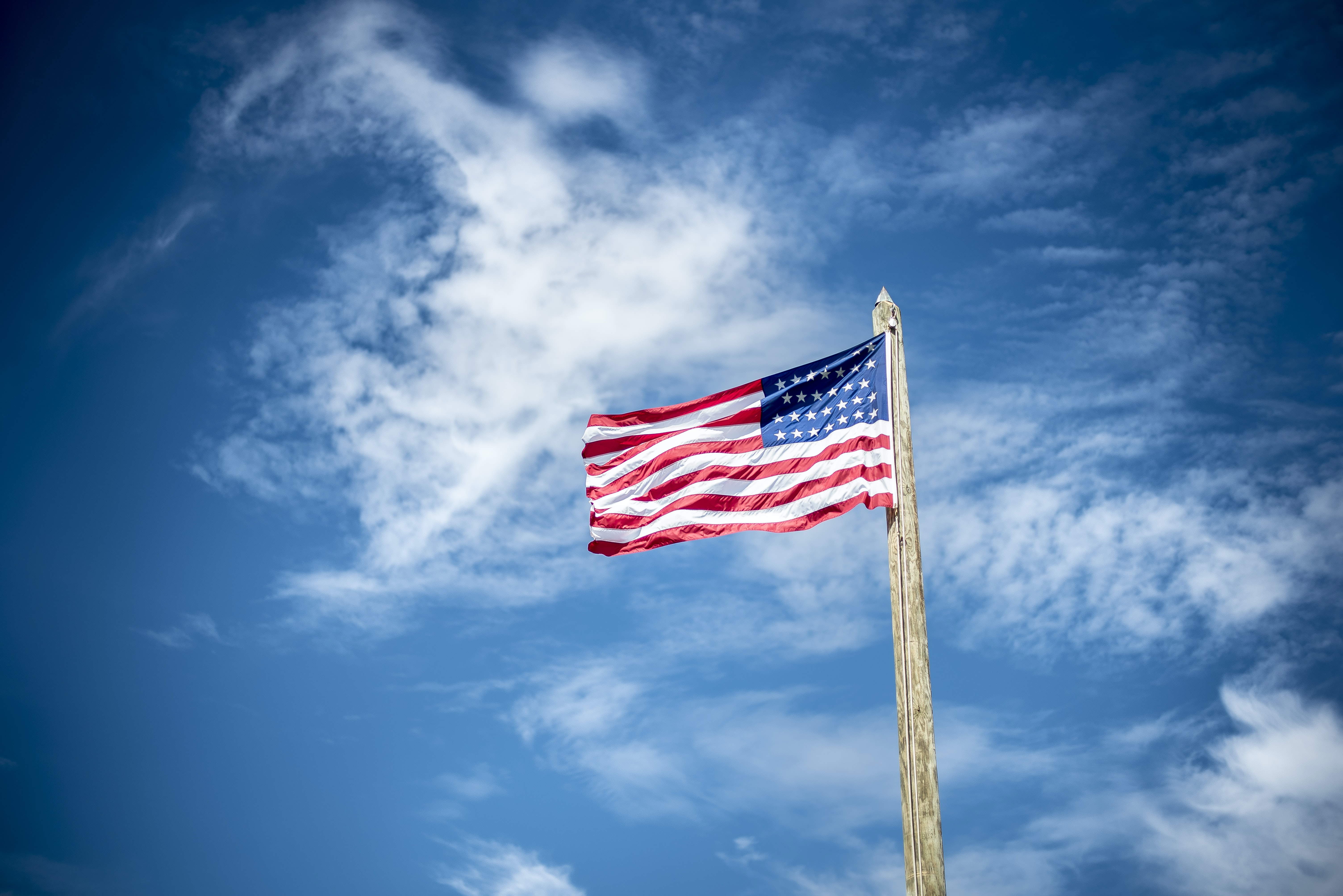 An American flag flying on a log pole against a blue sky with wispy clouds