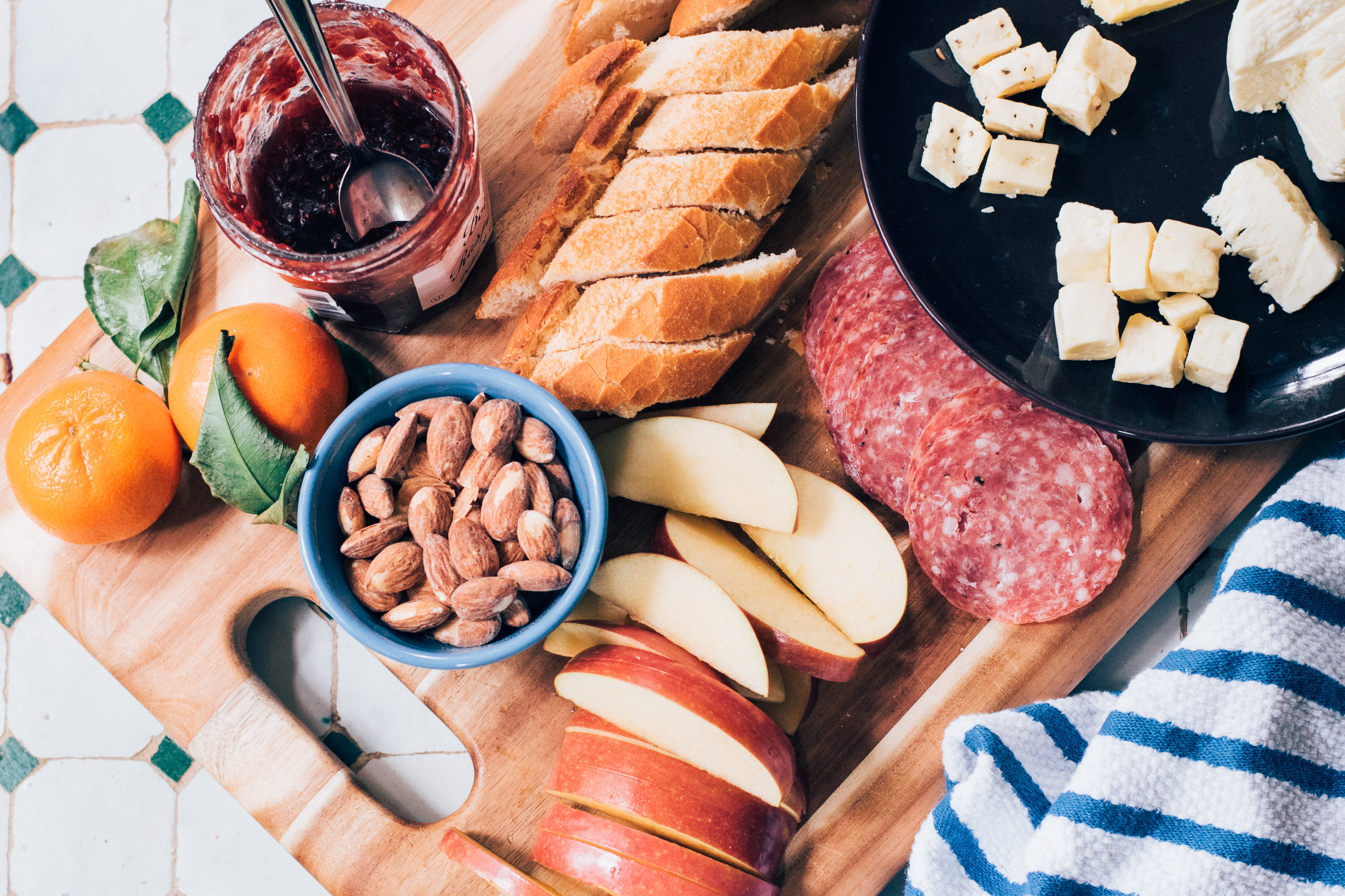 An overhead shot of a cutting board with almonds, fruit, bread and slices of salami on it