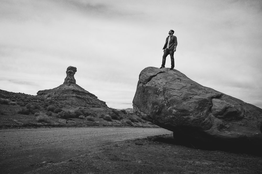 grayscale photo of man standing on rock formation