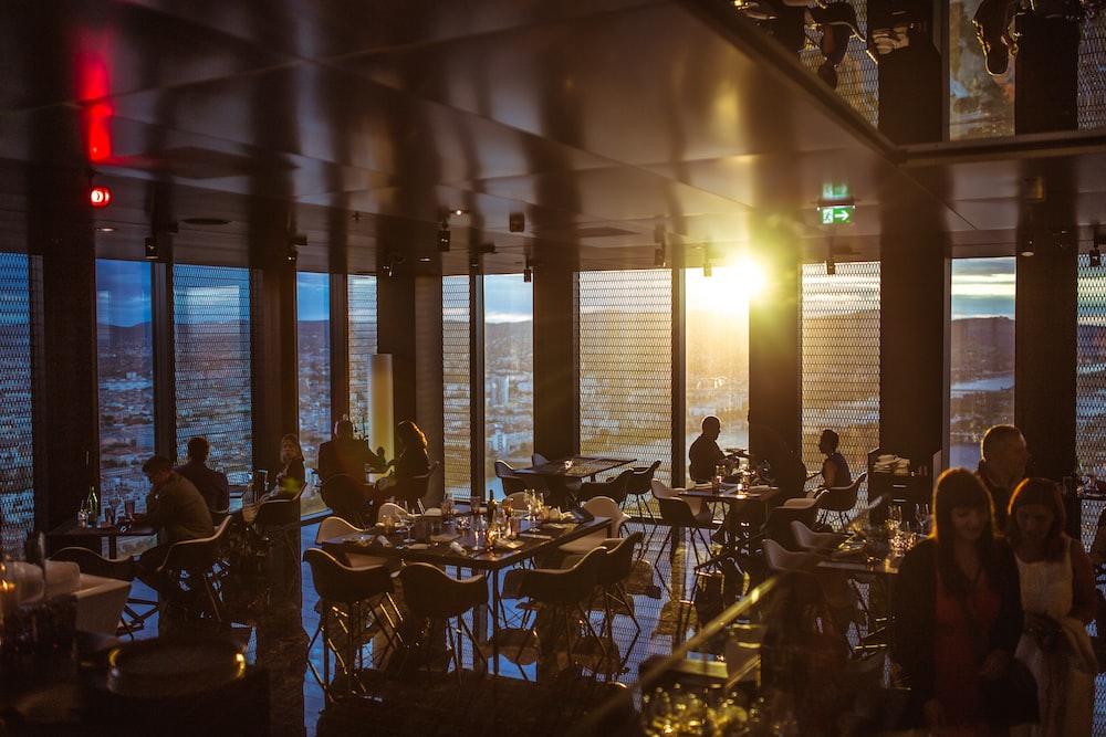 people gathering inside cafe during golden hour