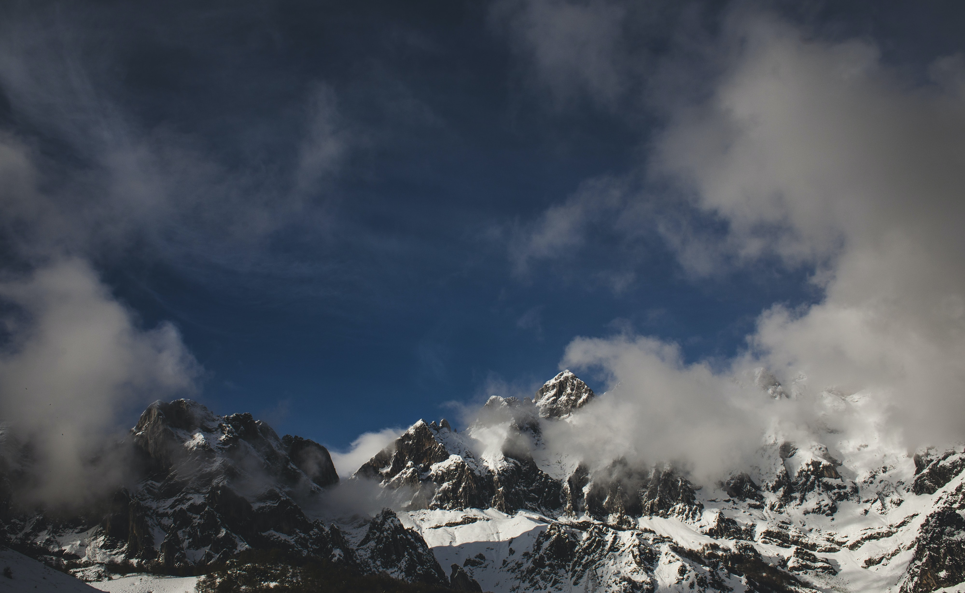 Clouds shrouding a jagged snow-covered mountain ridge in Picos de Europa