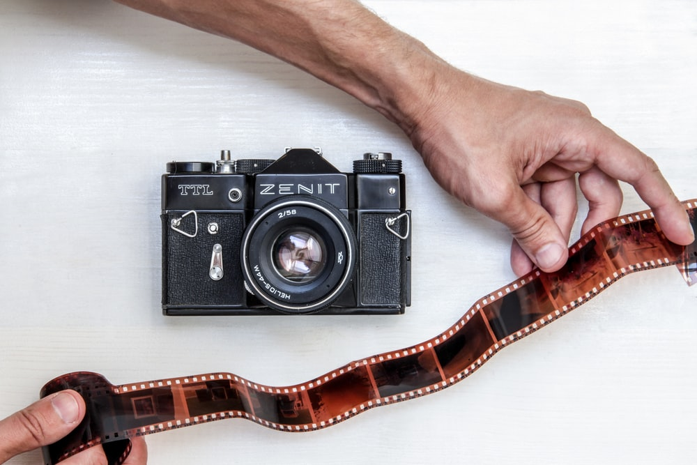 flat lay photography of person showing photo film beside Zenit DSLR camera