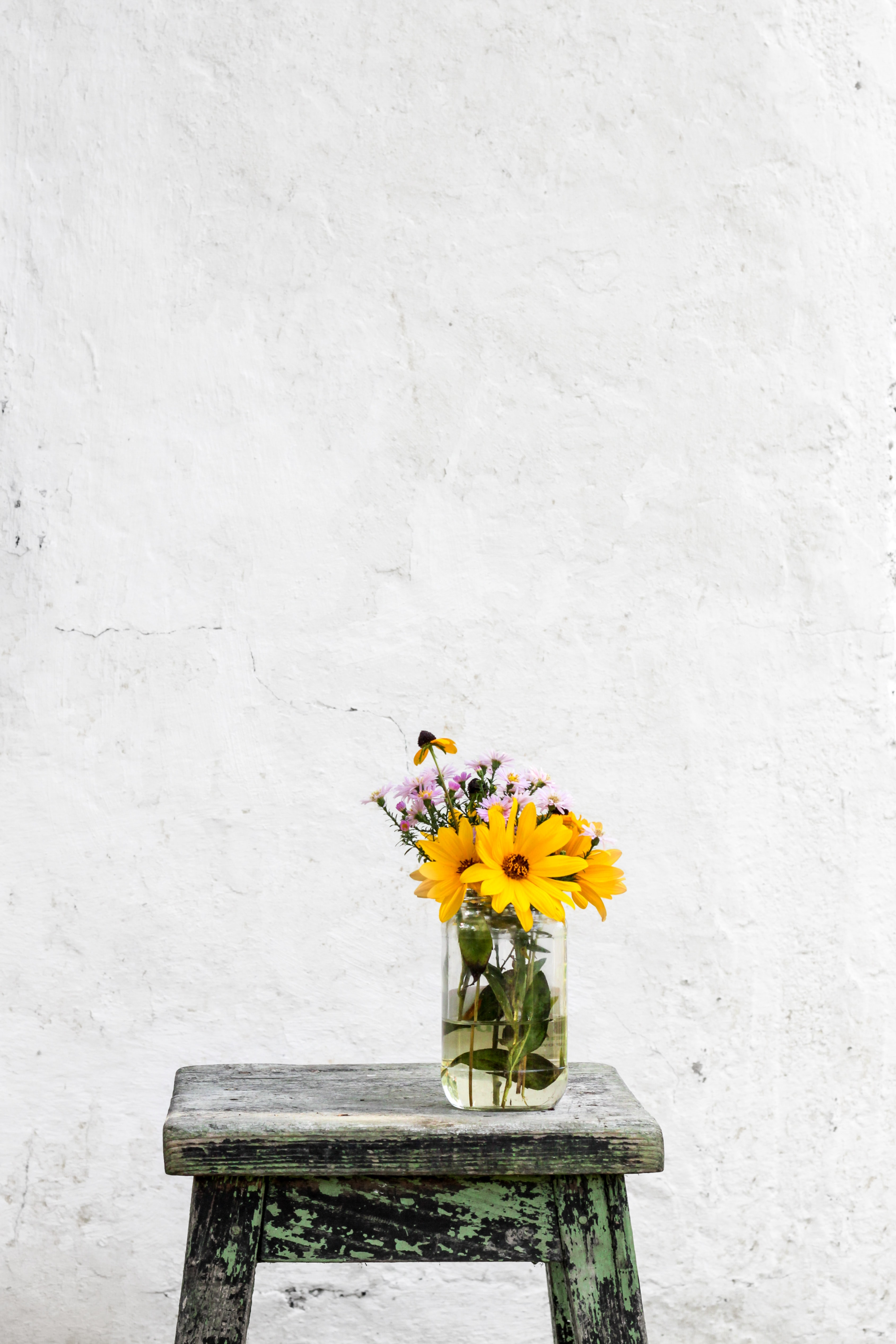 A glass vase with large yellow and small pink flowers on a worn-out stool against an old white wall
