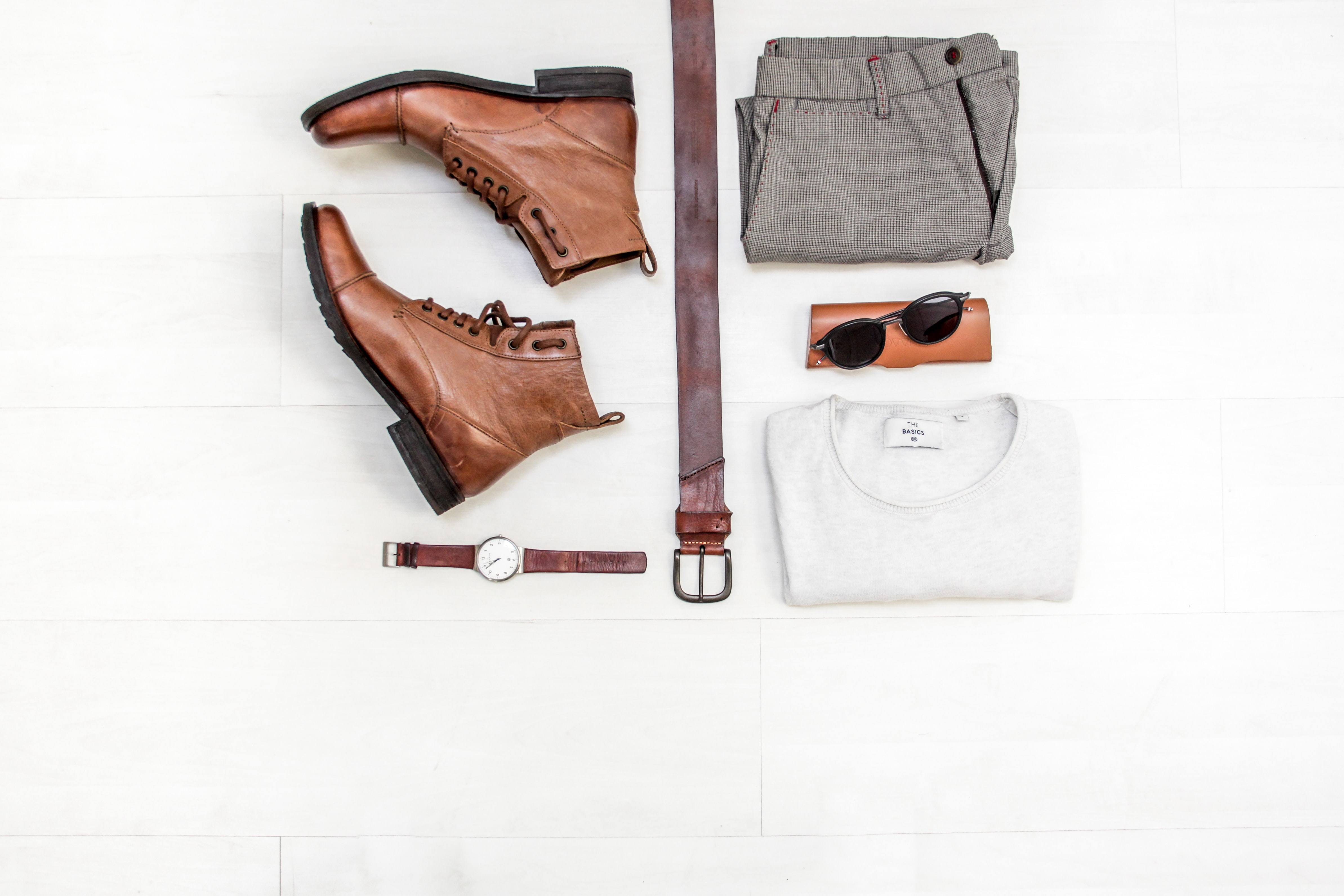 Top down view of a pair of leather boots, a leather belt, a leather analogue watch, grey slacks, sunglasses and case, and a white tee on a white surface