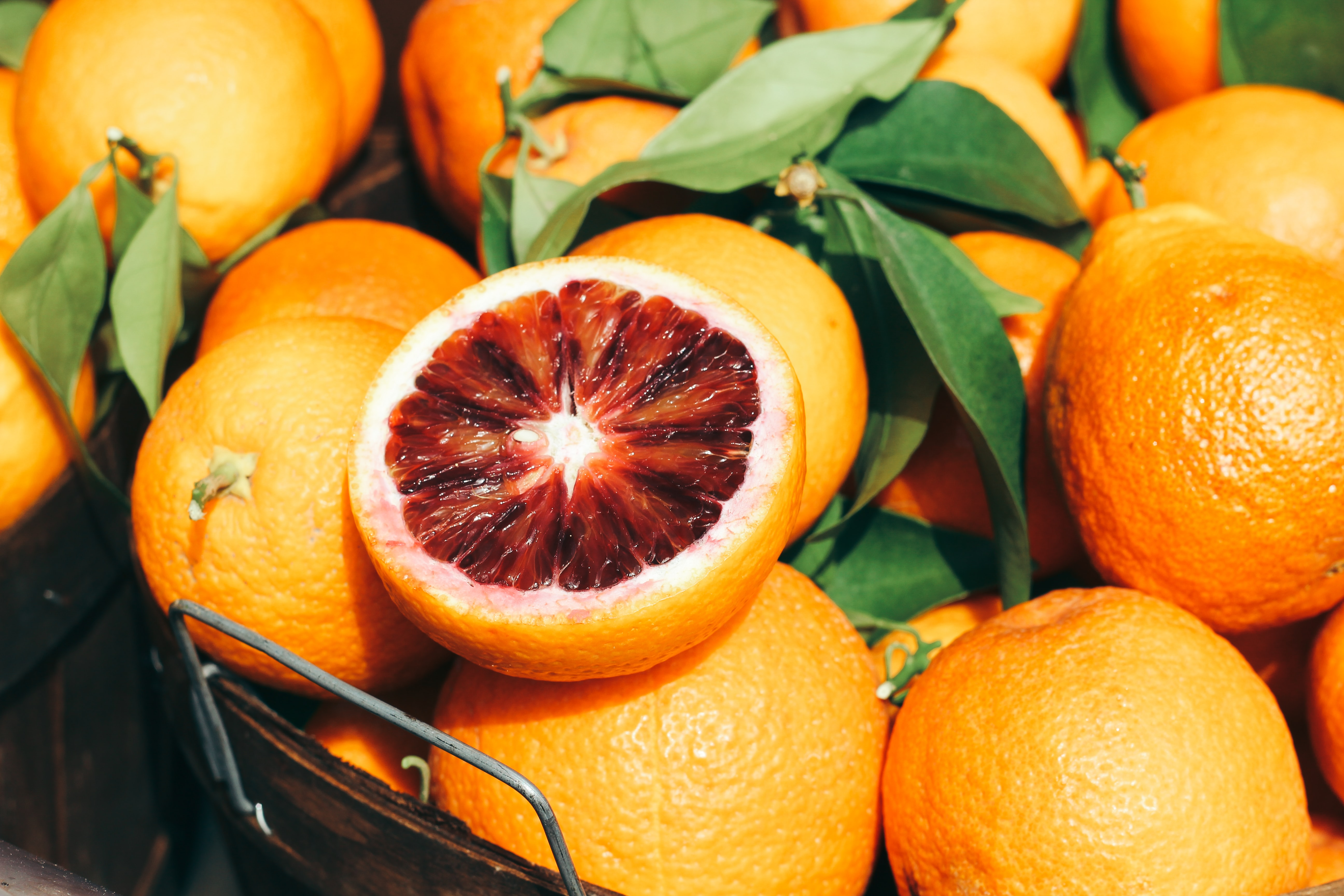 Basket of blood oranges and leaves with one cut in half