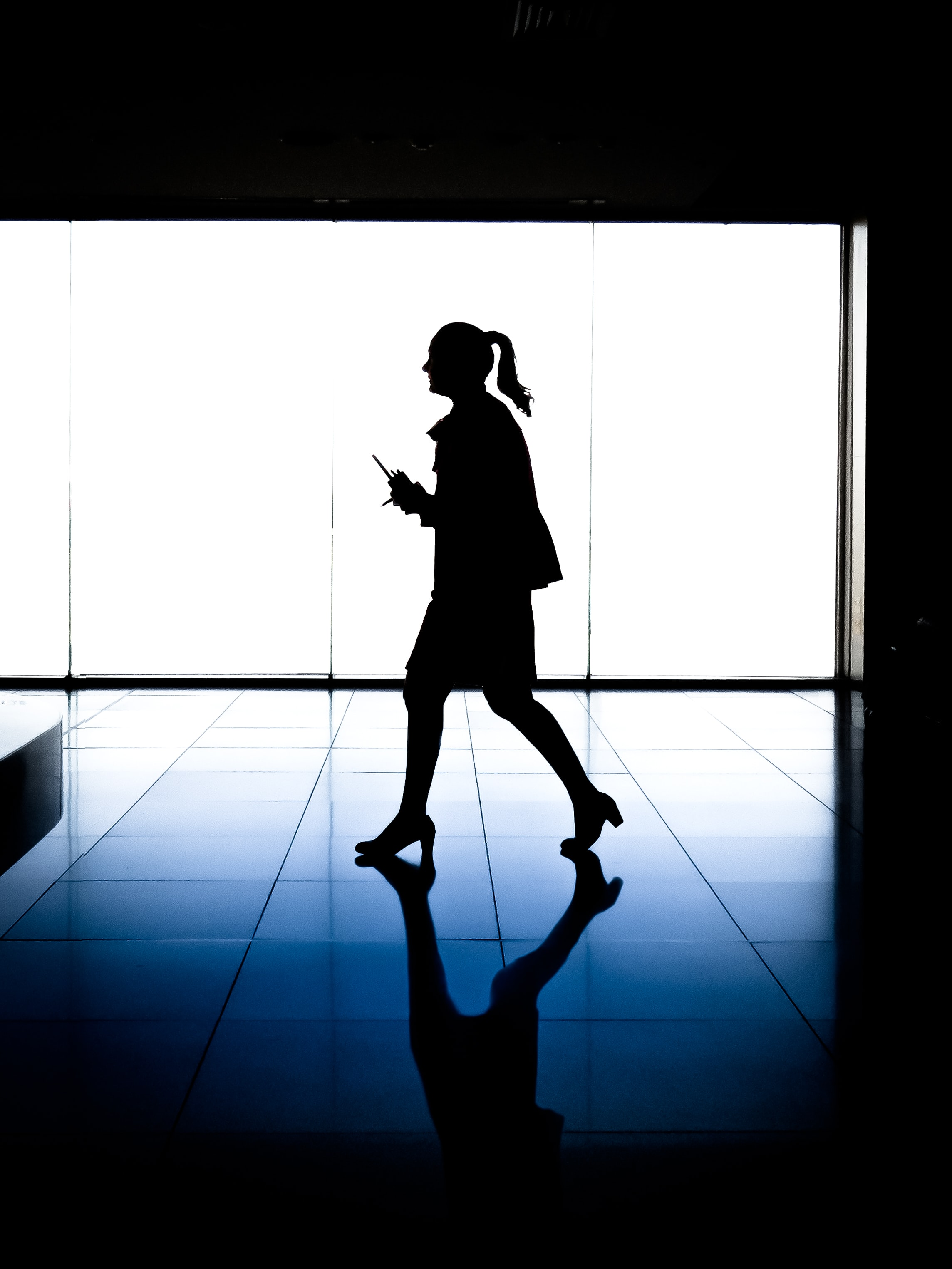 silhouette of woman walking inside building