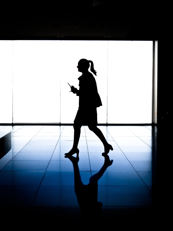 silhouette of woman walking inside building