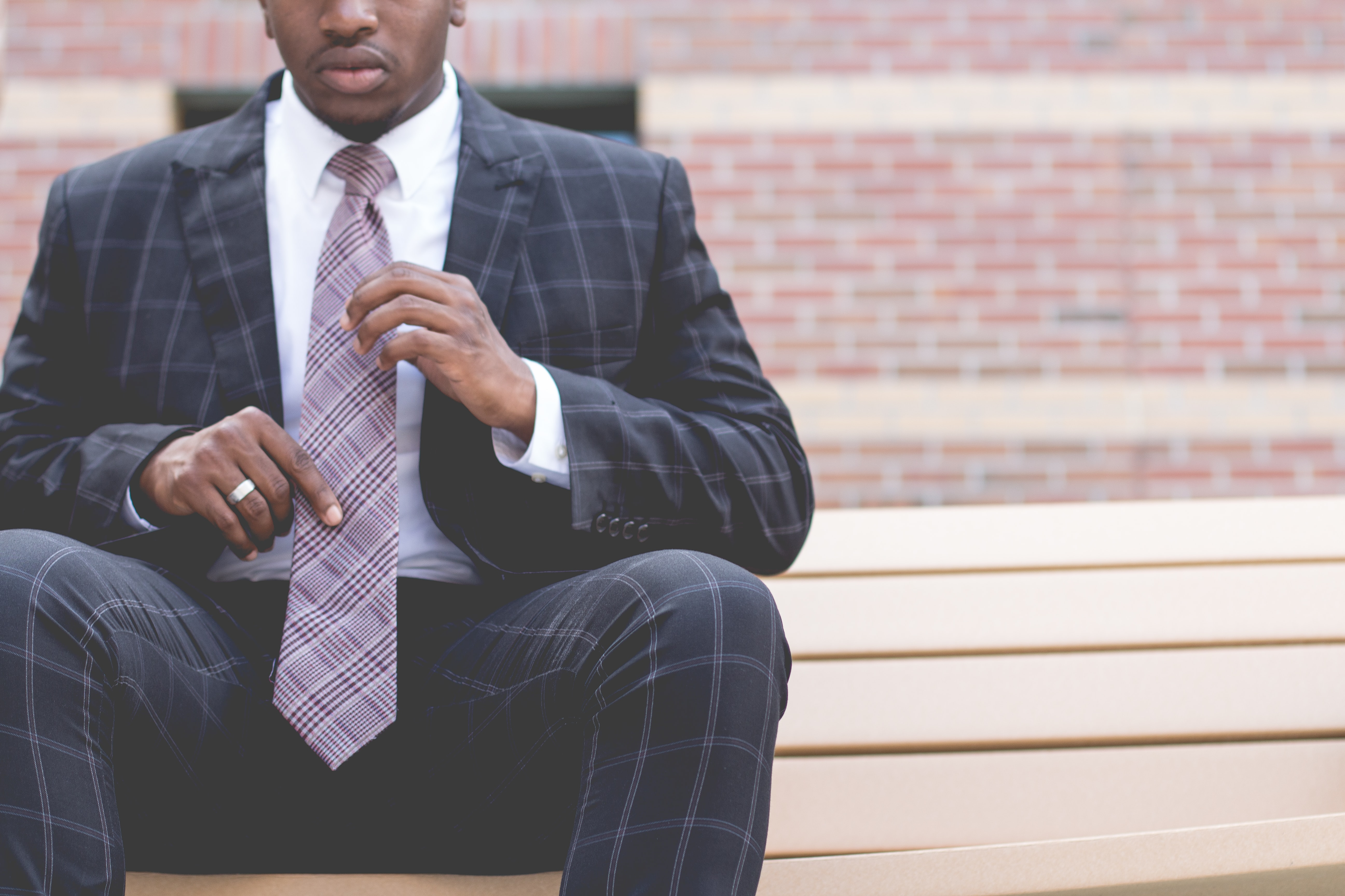 A man in a plaid suit sitting on a bench