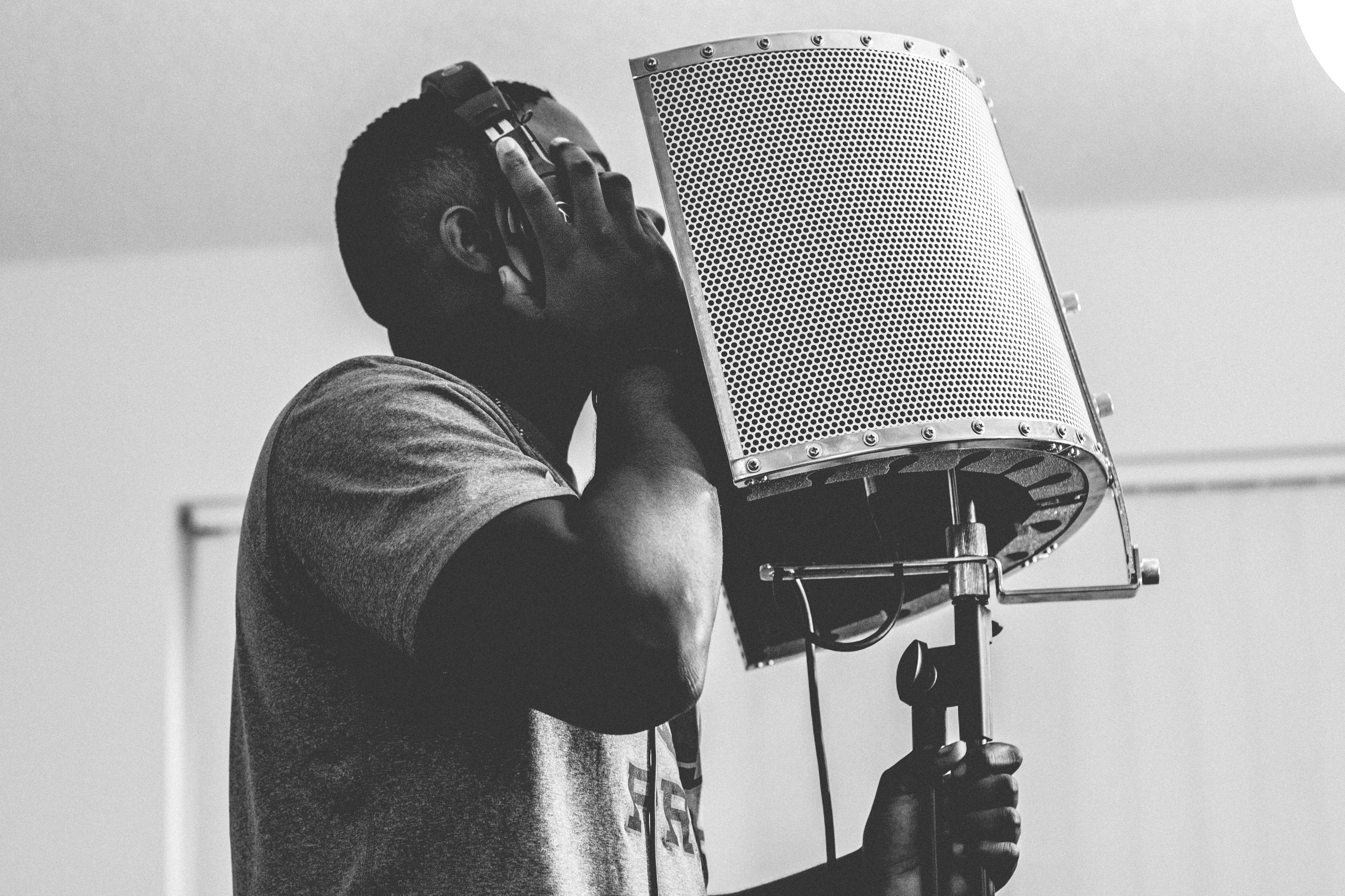 man wearing headphones while singing in front of microphone inside studio