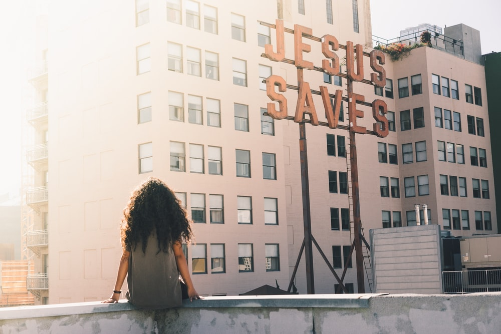 woman in gray top sitting on a building's edge