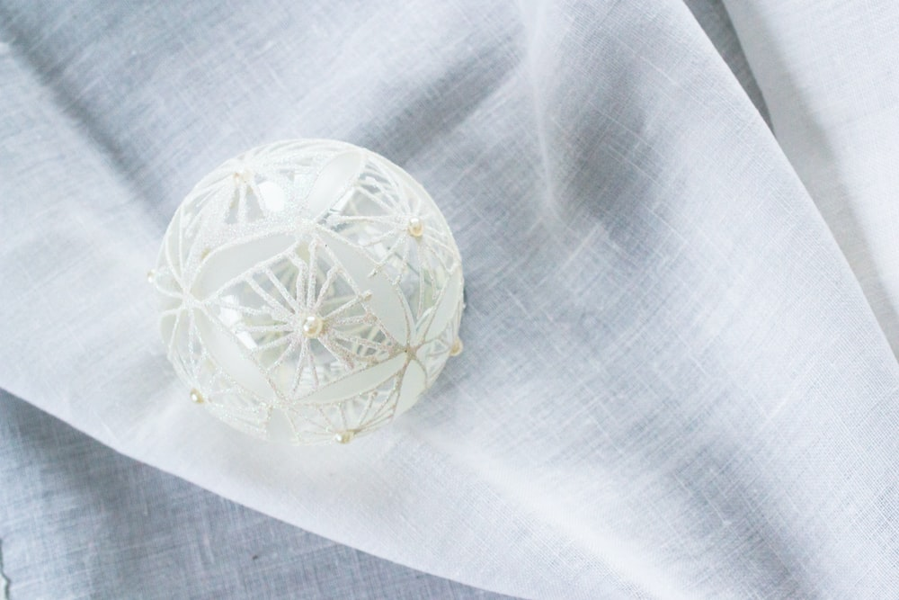 white lace Christmas bauble on white garment