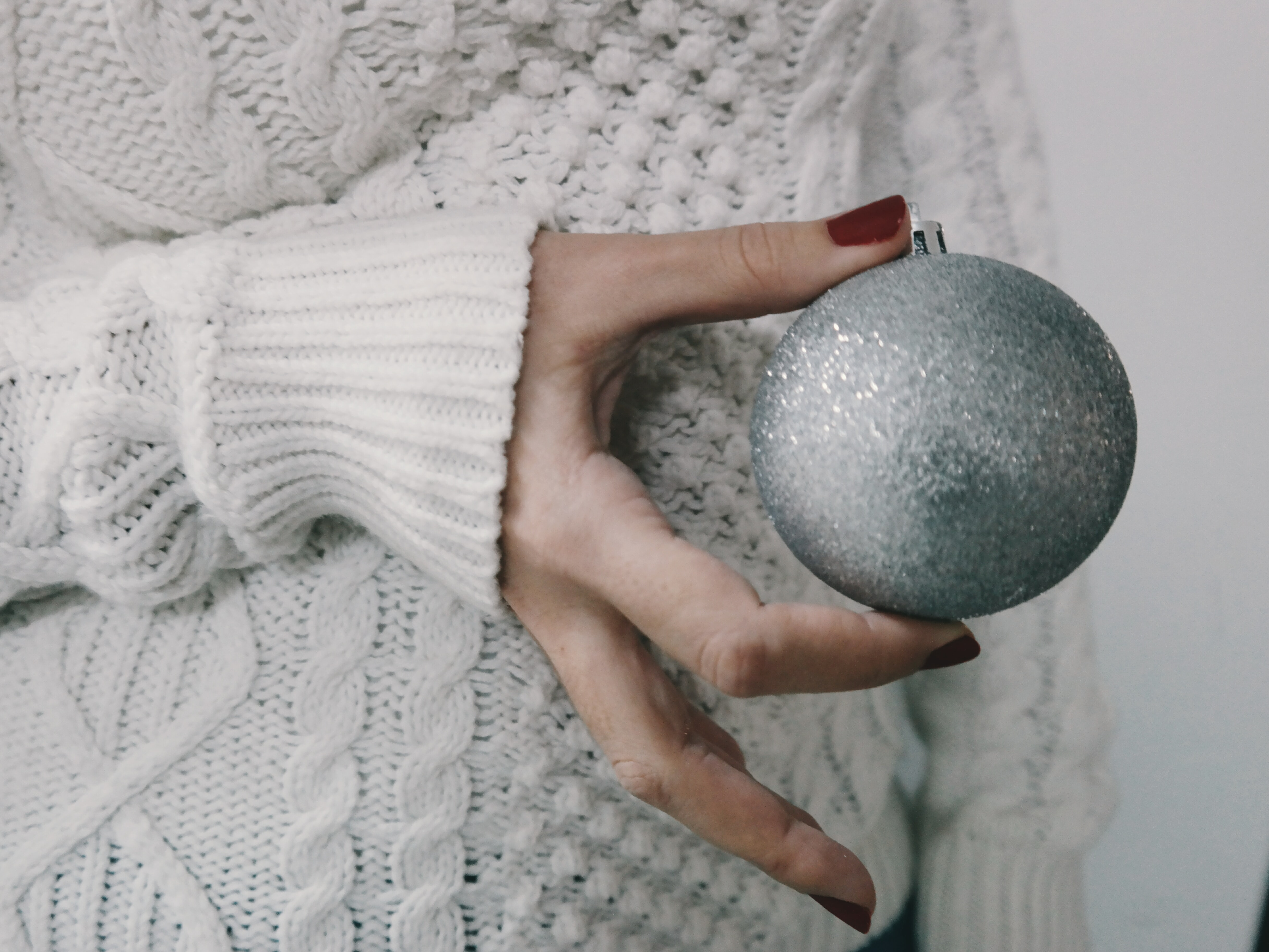 A person wearing a knitted sweater holding a silver Christmas ornament.
