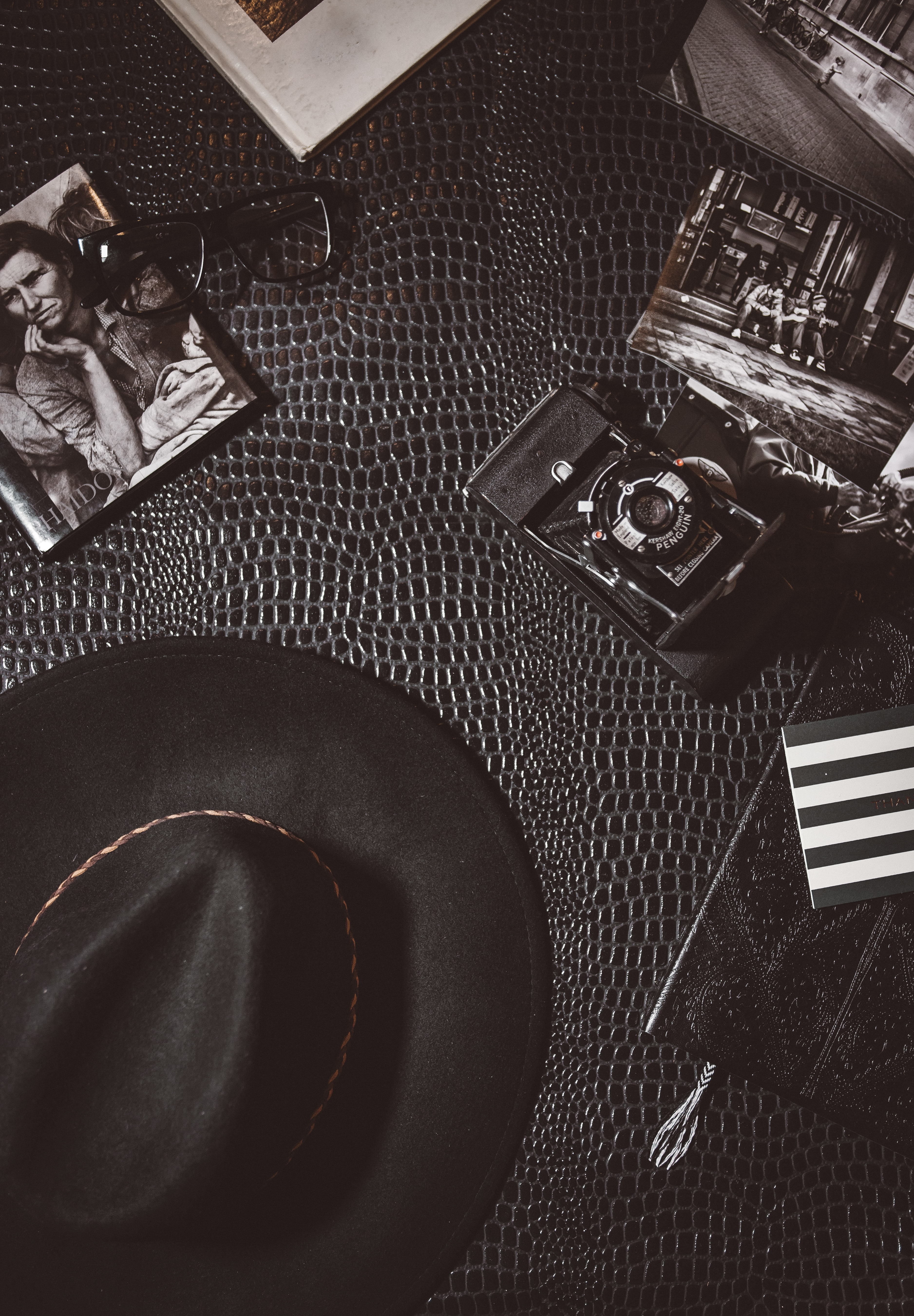 Vintage shot of hat, camera, glasses and monochrome photos lying on leather surface