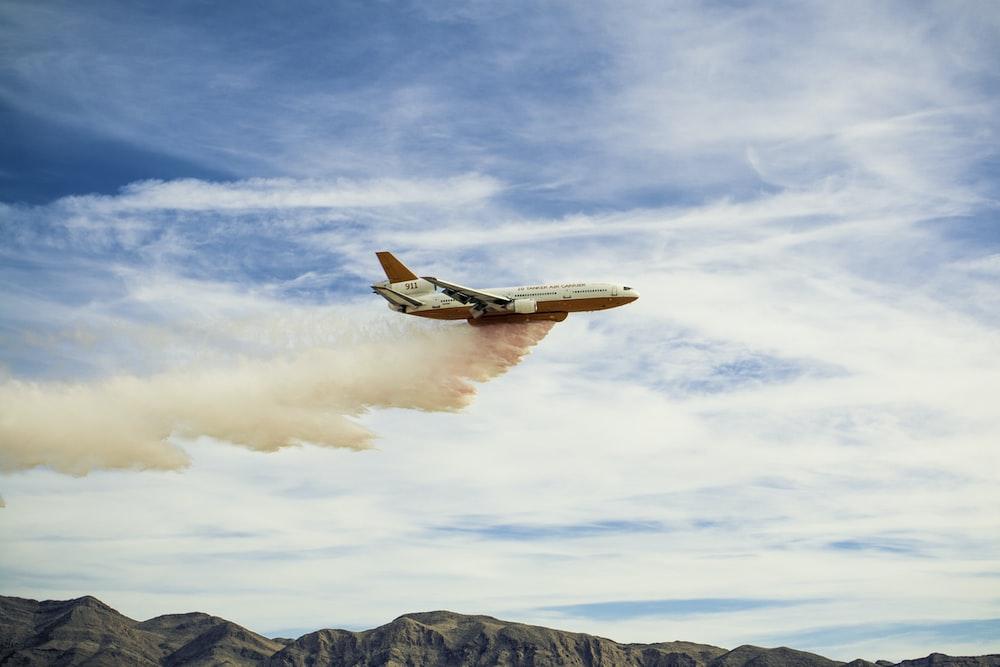 white plane spreading pink smoke