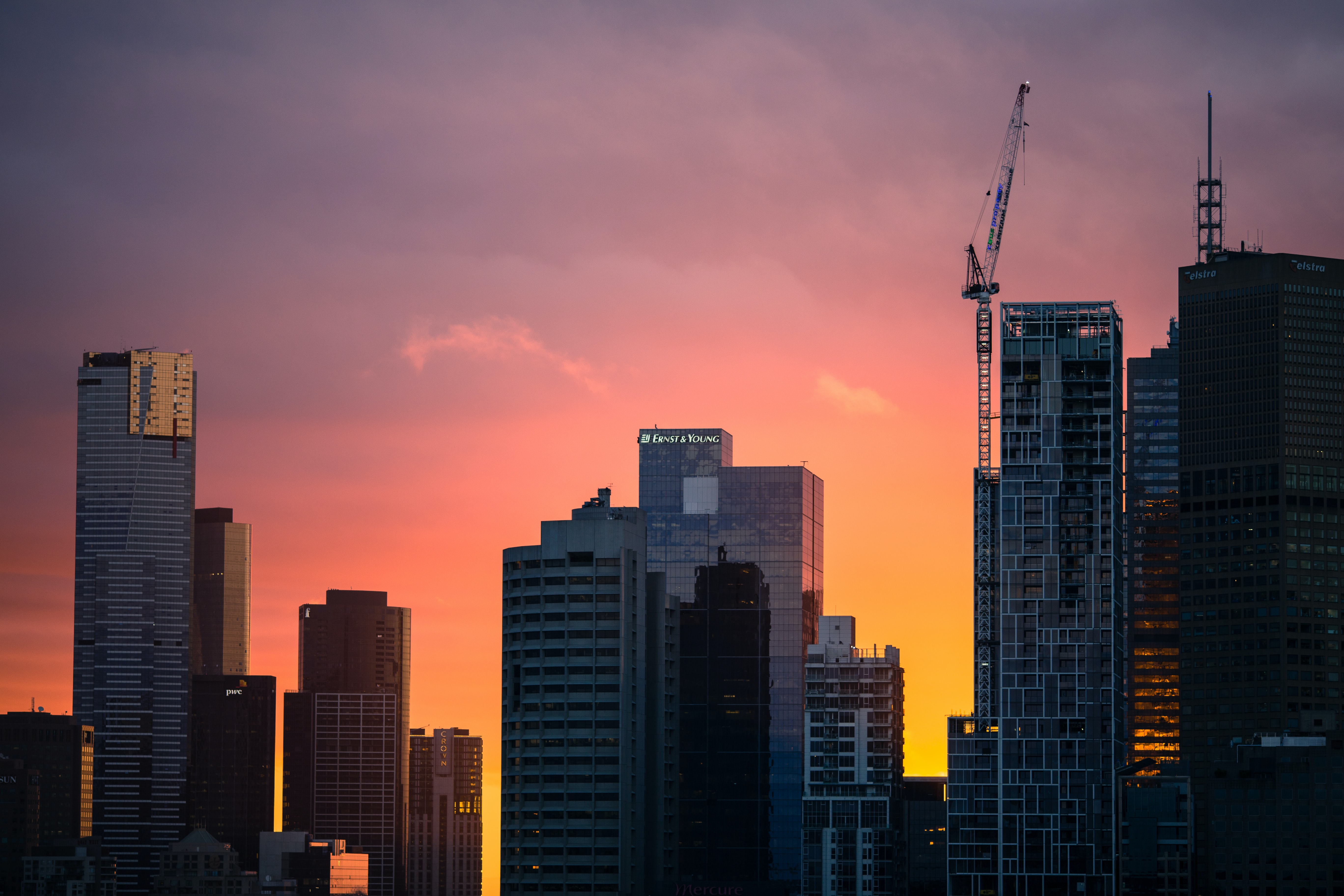 A pink and orange sunset behind the skyscrapers of Melbourne