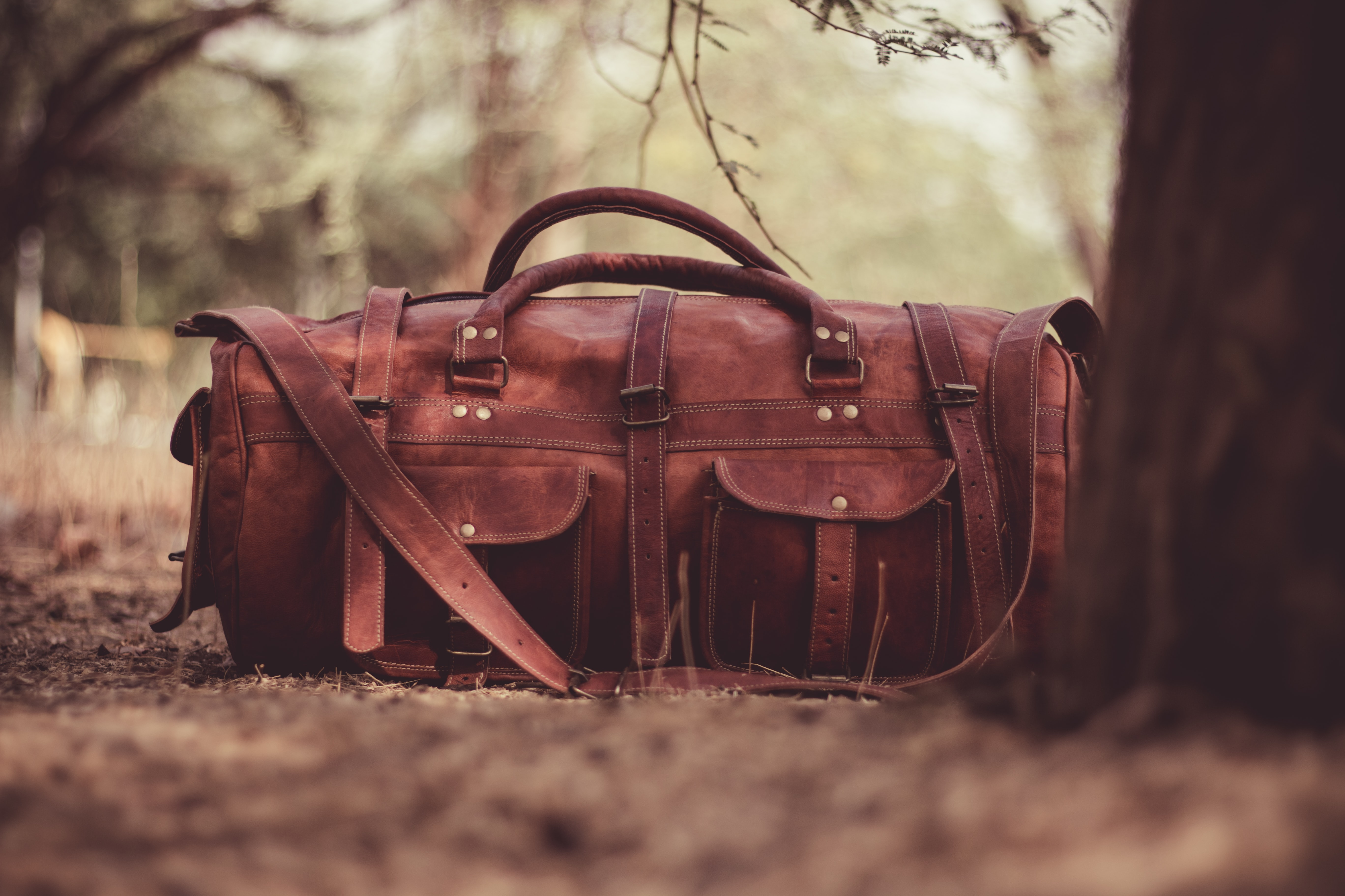 A leather duffel bag on the forest floor under a tree