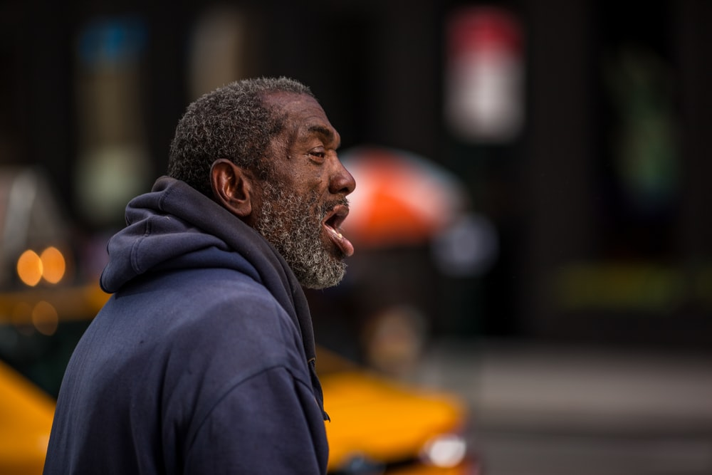 man in black hoodie standing on street during daytime