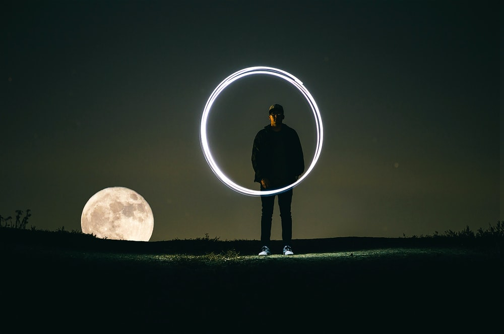 man standing on hill during full moon