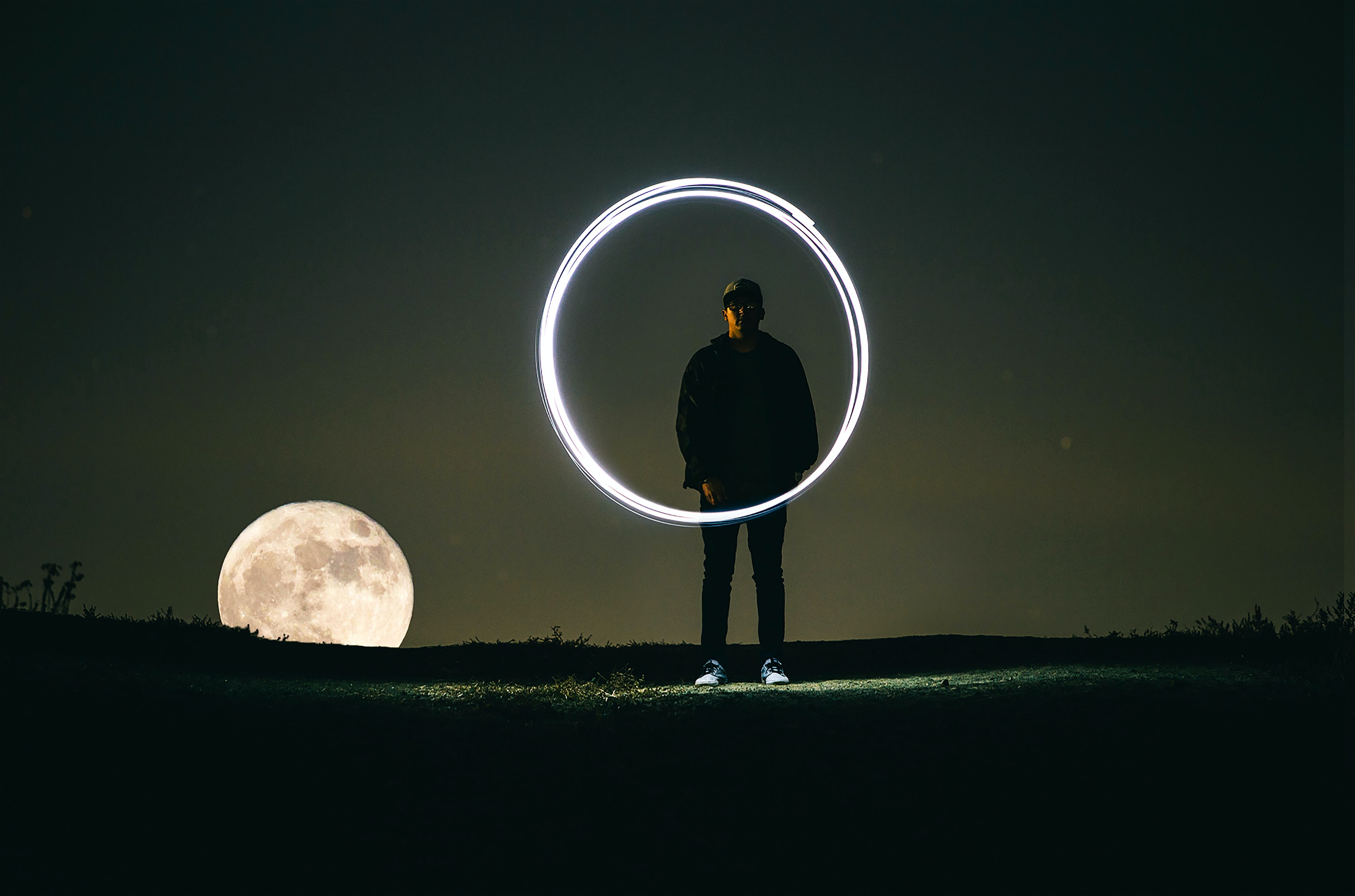 Long exposure shot of a man creating a circle of light, as the moon rises behind