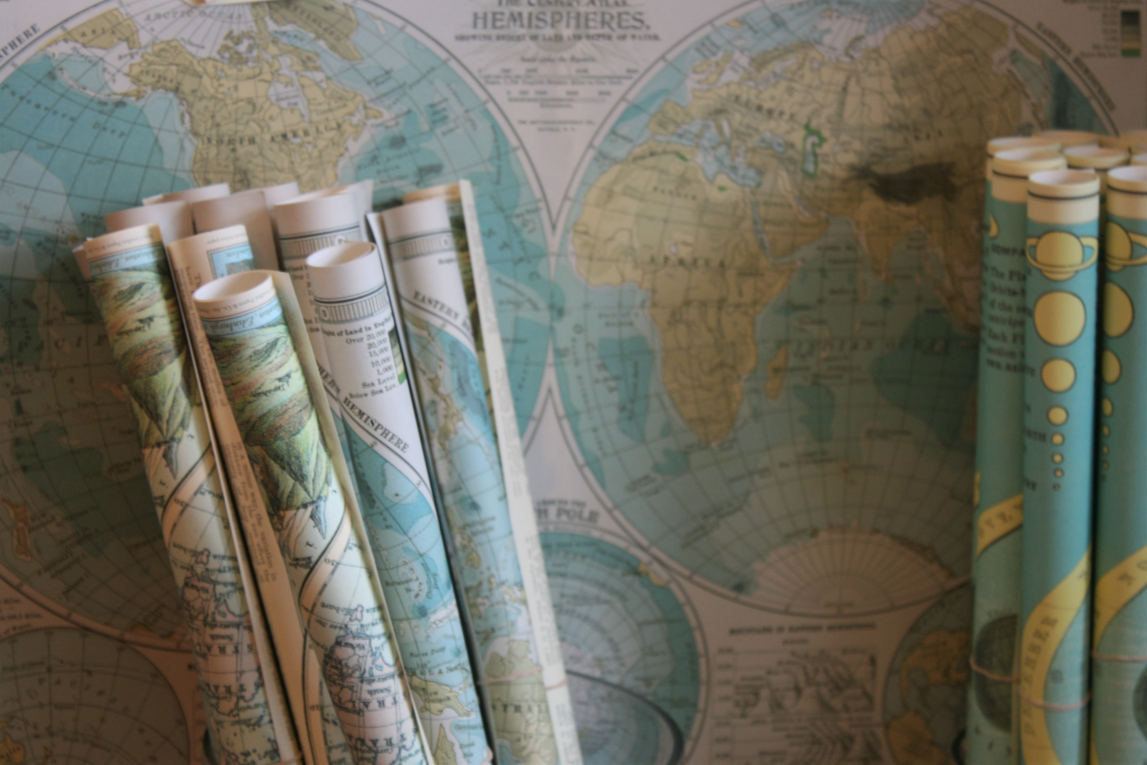 Rolled maps standing against a world map on the wall