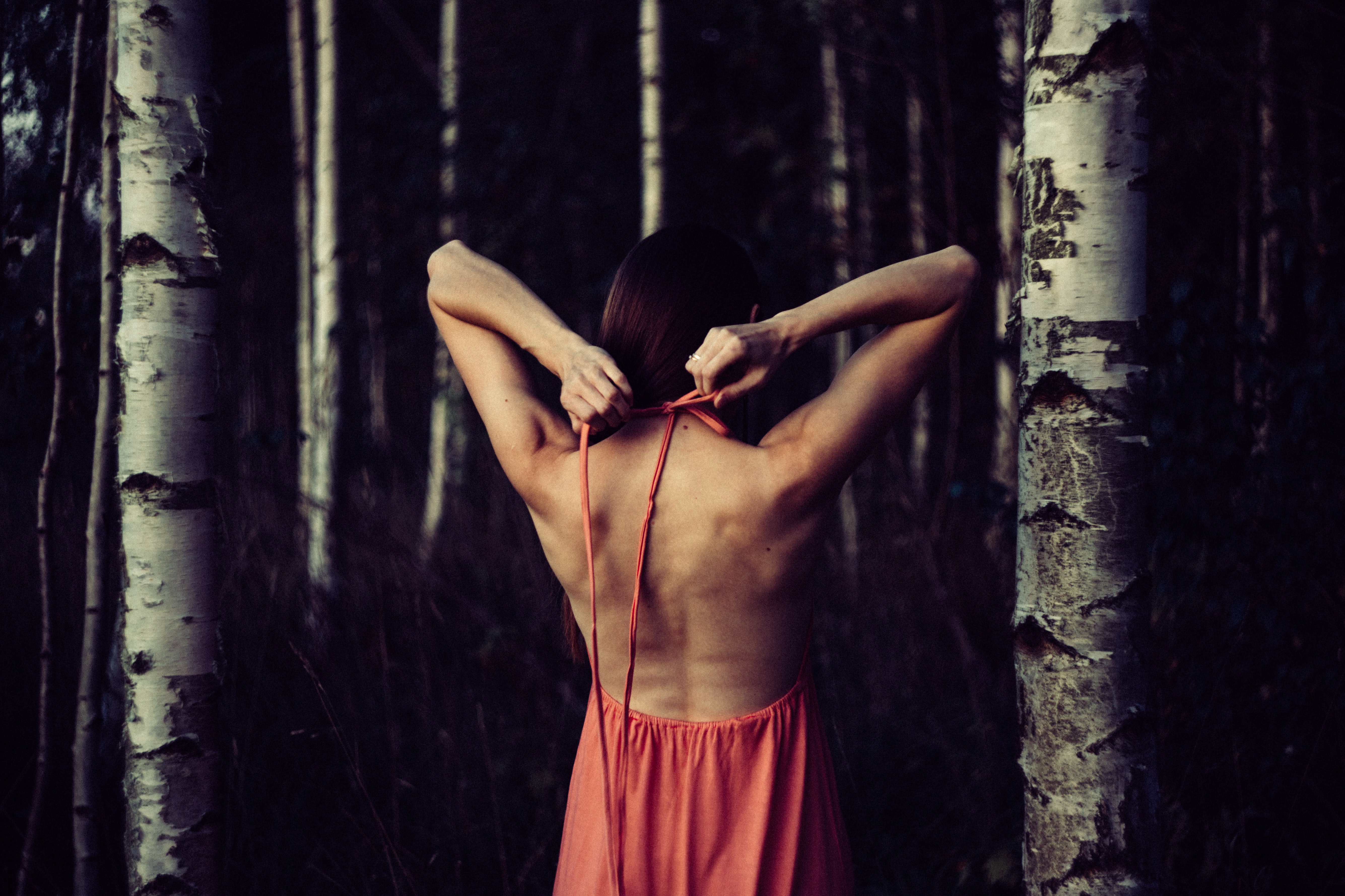 A girl stretching with her arms behind her back inside a forest.
