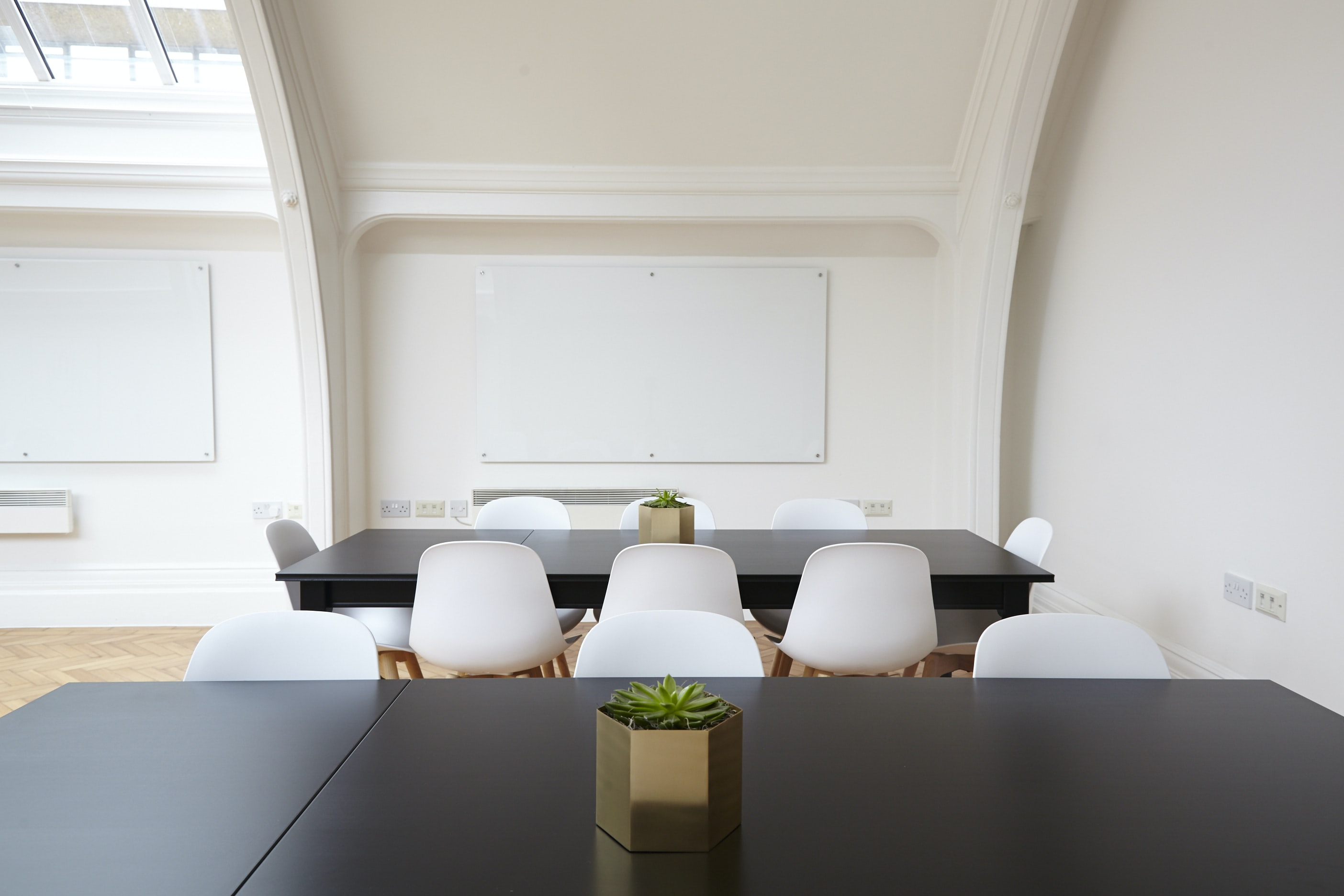An elegant conference room with two whiteboards, black tables and white chairs