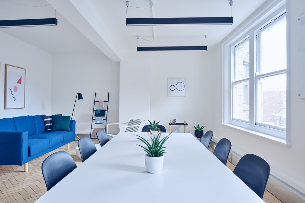 A minimalist interior with a long white table and a blue sofa