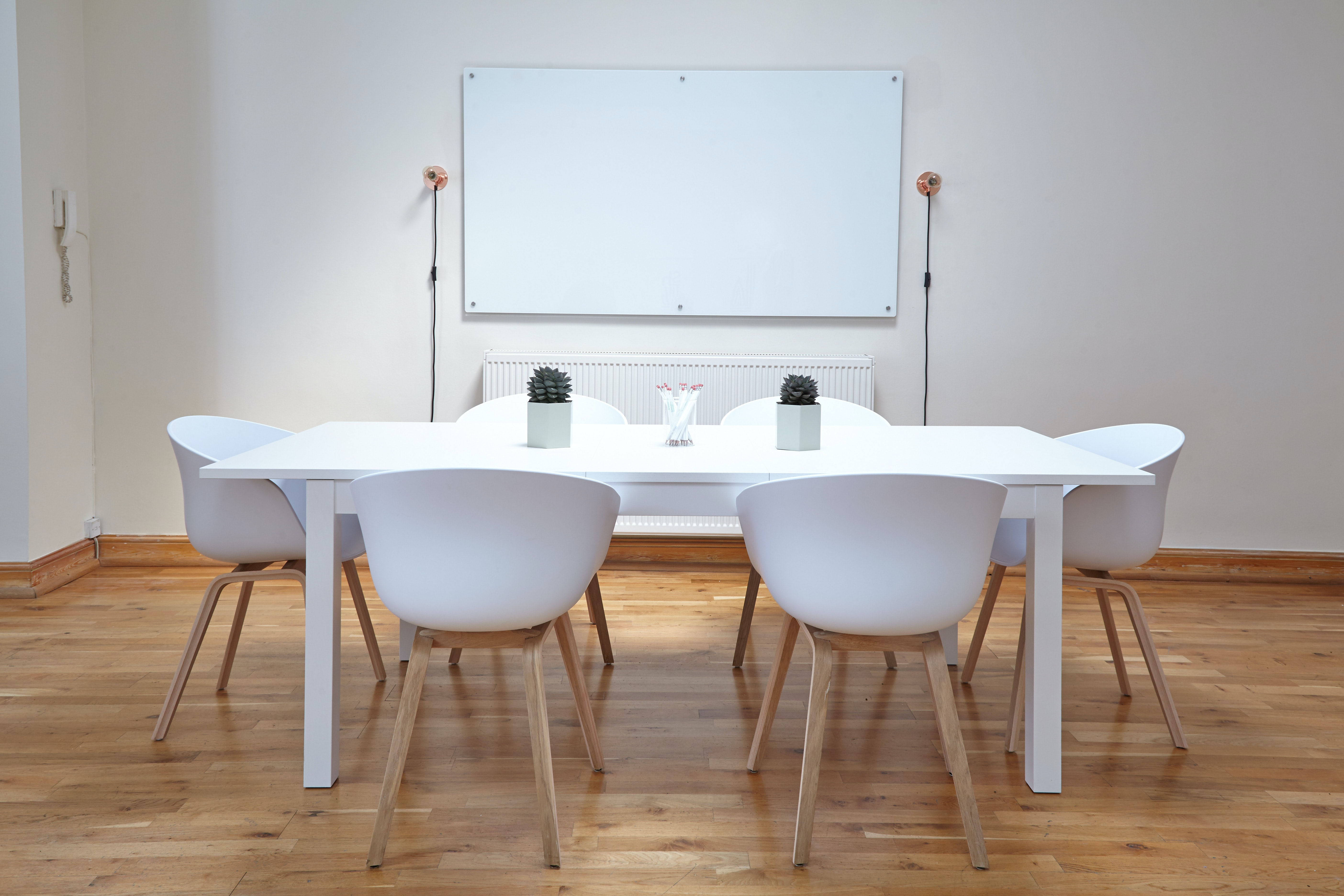 White chairs near a white table in a small conference room with a whiteboard